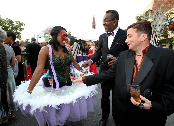 Server Jinene Thompson offers champagne from the hoop platform of her dress to Ed Williams, center, and Peter Davis at the annual Curtain Up! celebration Friday evening in the Theater District. (Robert Kirkham/Buffalo News)