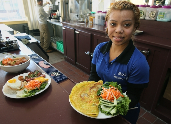 Server Linda Nguyen is shown with a pancake dish at Pho Dollar restaurant on West Ferry Street. (Charles Lewis/Buffalo News)