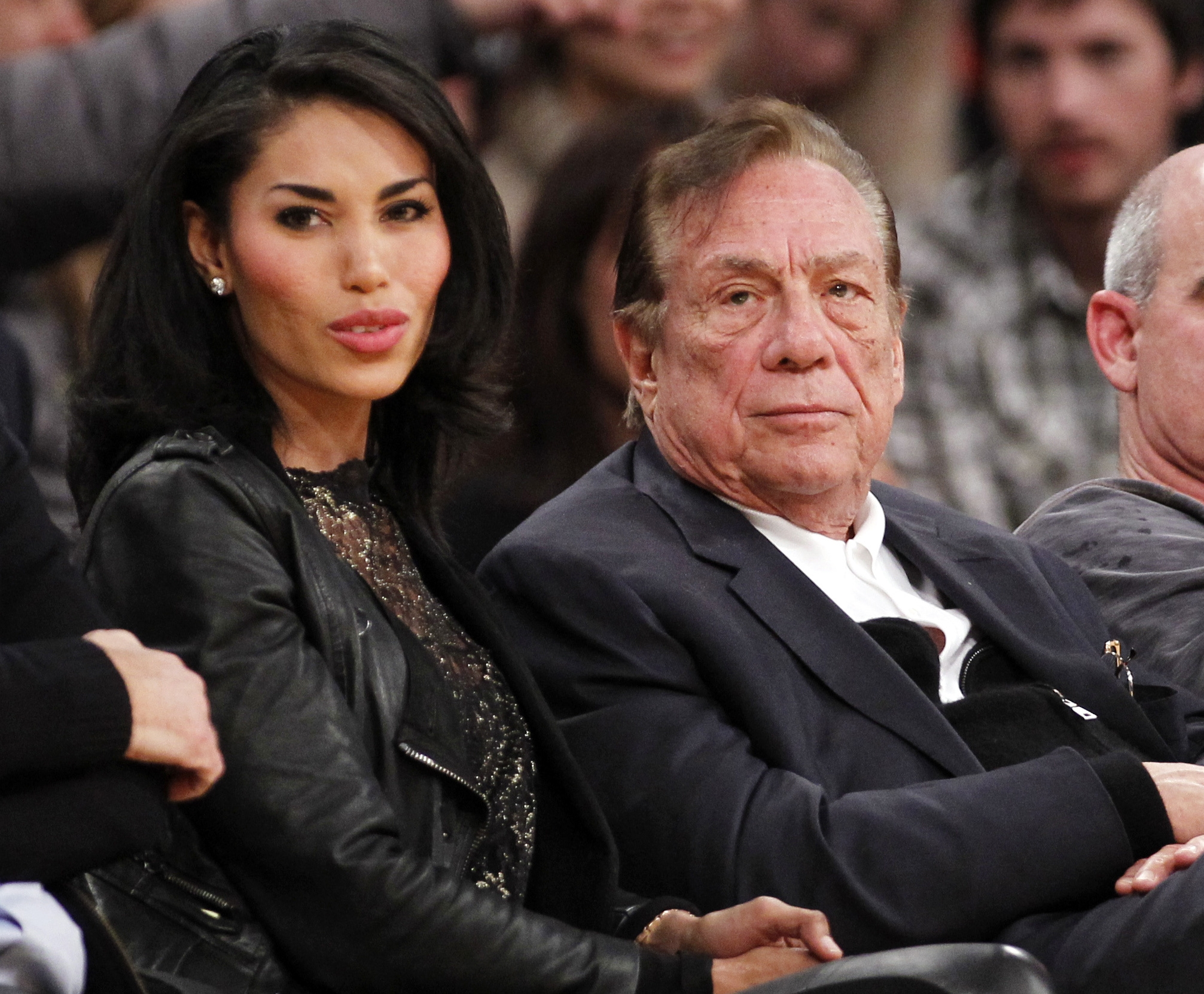 Clippers owner Donald Sterling, with V. Stiviano at a preseason game, faces a ban and a $2.5 million fine for racist remarks