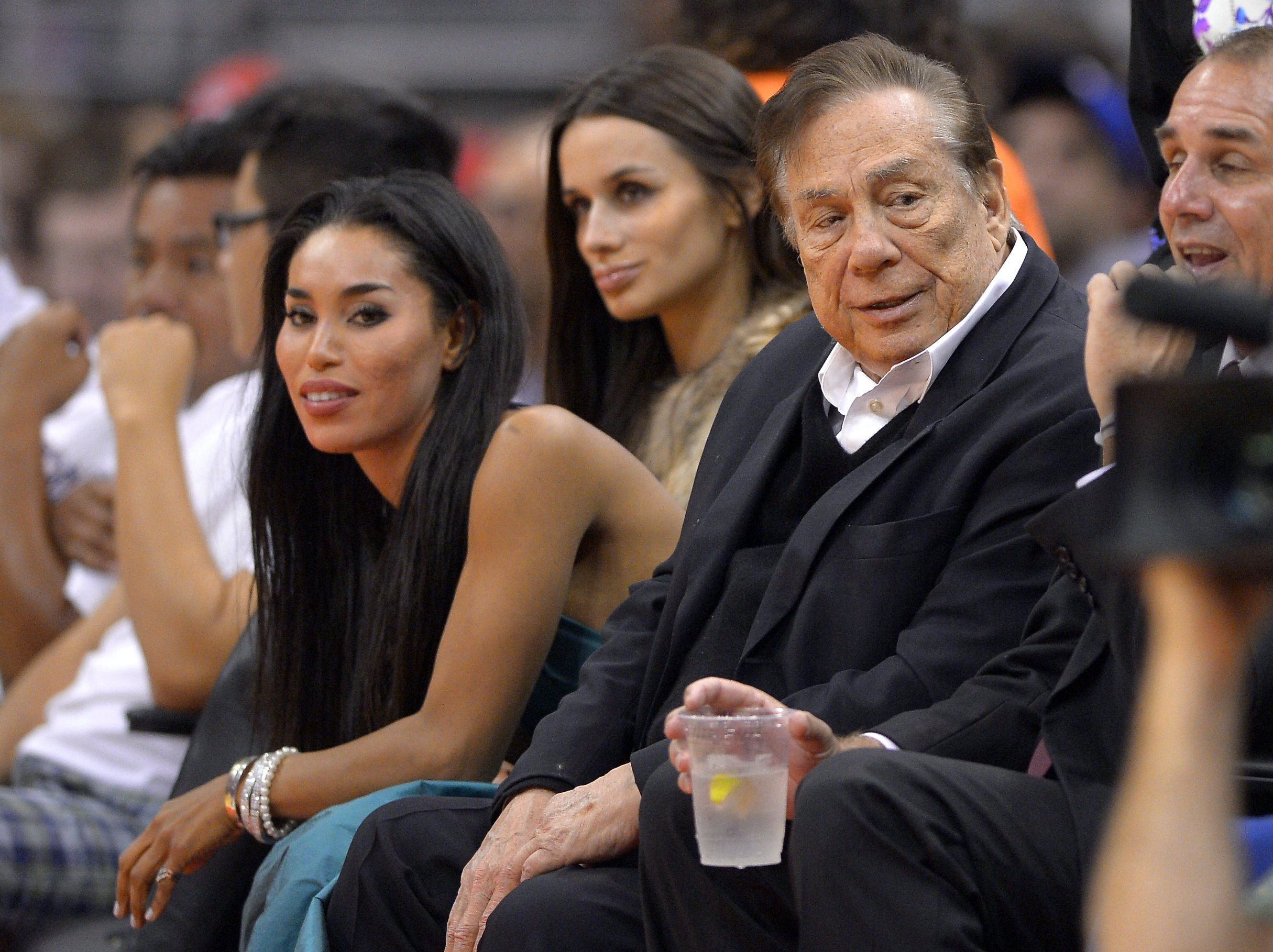 Los Angeles Clippers owner Donald Sterling, right, and V. Stiviano, left, watch the Clippers play the Sacramento Kings during an October game. NBA Commissioner Adam Silver on Tuesday banned Sterling for life from association with the NBA or the Clippers.