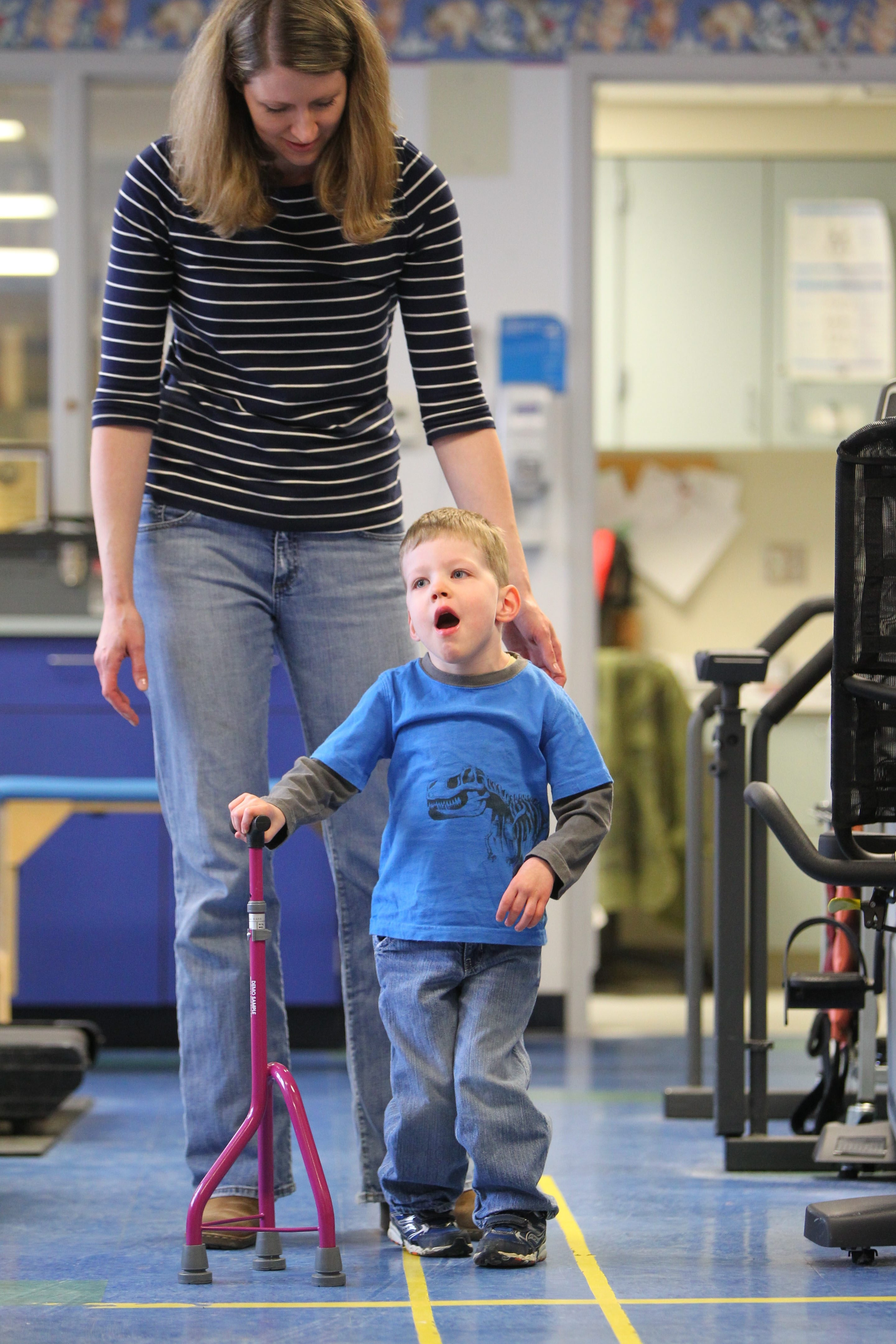 Austin Collier, 3 years old, works on walking with his mother Stephanie Collier, back, and physical therapist Dawn Shaflucas, not shown, at the Robert Warner Rehab Center in Women and Children's hospital in Buffalo Tuesday, April 15, 2014.