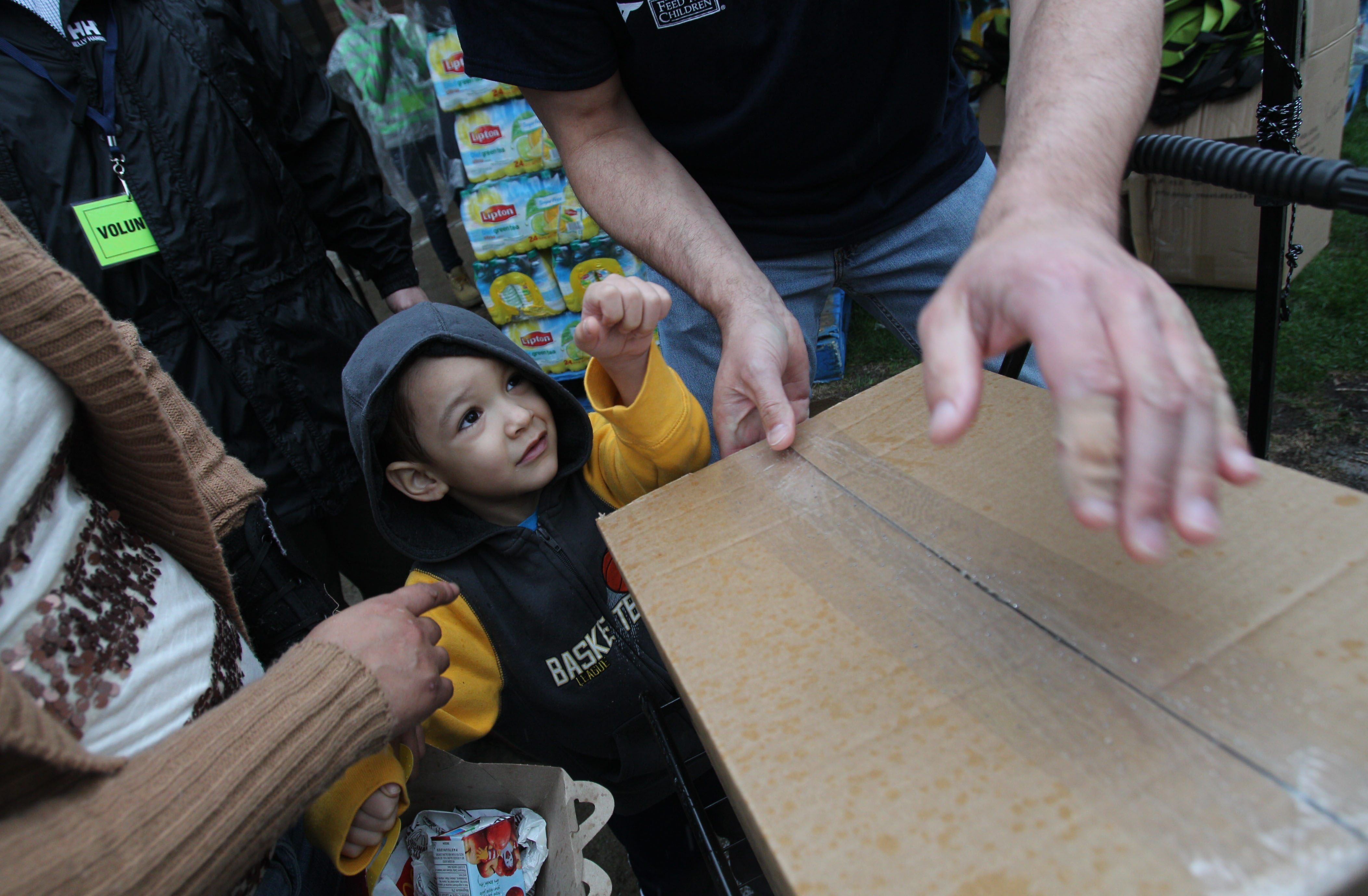 Eight hundred families in Buffalo's poorest neighborhood, on the lower West Side, are given food April 24 at the Belle Center. Here, Evan Camilo, 3, makes sure his mom chooses the beverage he likes. The Belle Center and the Buffalo Dream Center were organizers for the event.