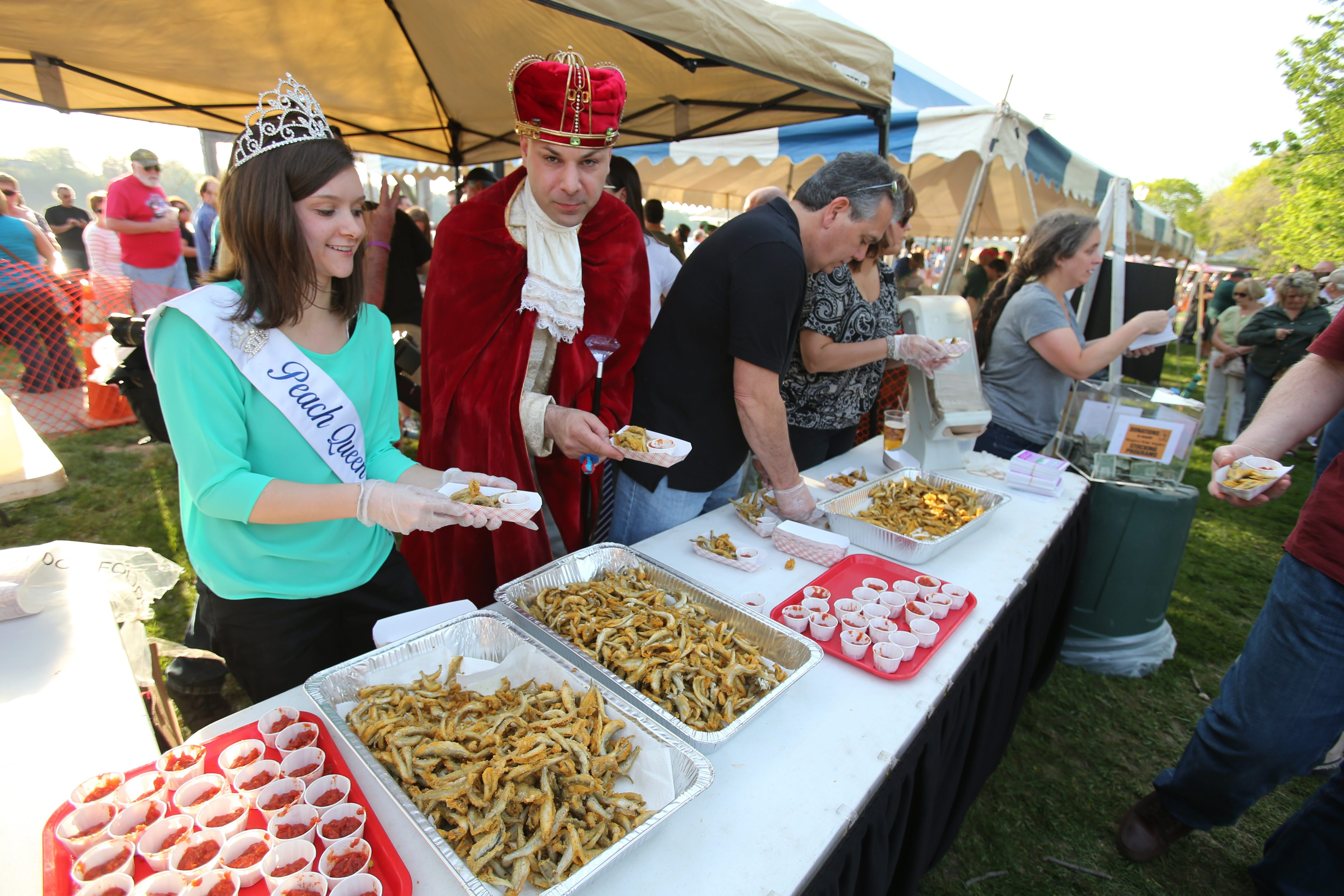 Niagara County Peach Queen Maggie Dorian, left, and Smelt King Ken Scibetta served some of the fried creatures at a recent Smelt Festival in Lewiston.