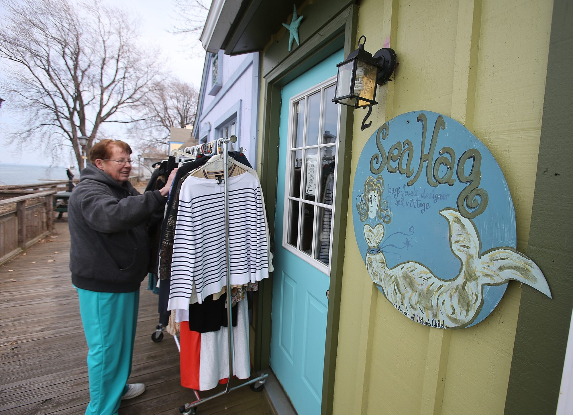 "Scotty Johnson arranges clothing outside The Sea Hag, a business she owns, as the Lakeview Village Shoppes in Olcott get ready for Saturday's opening of a season in which, the town liaison says, ""there's something going on here"" every weekend."
