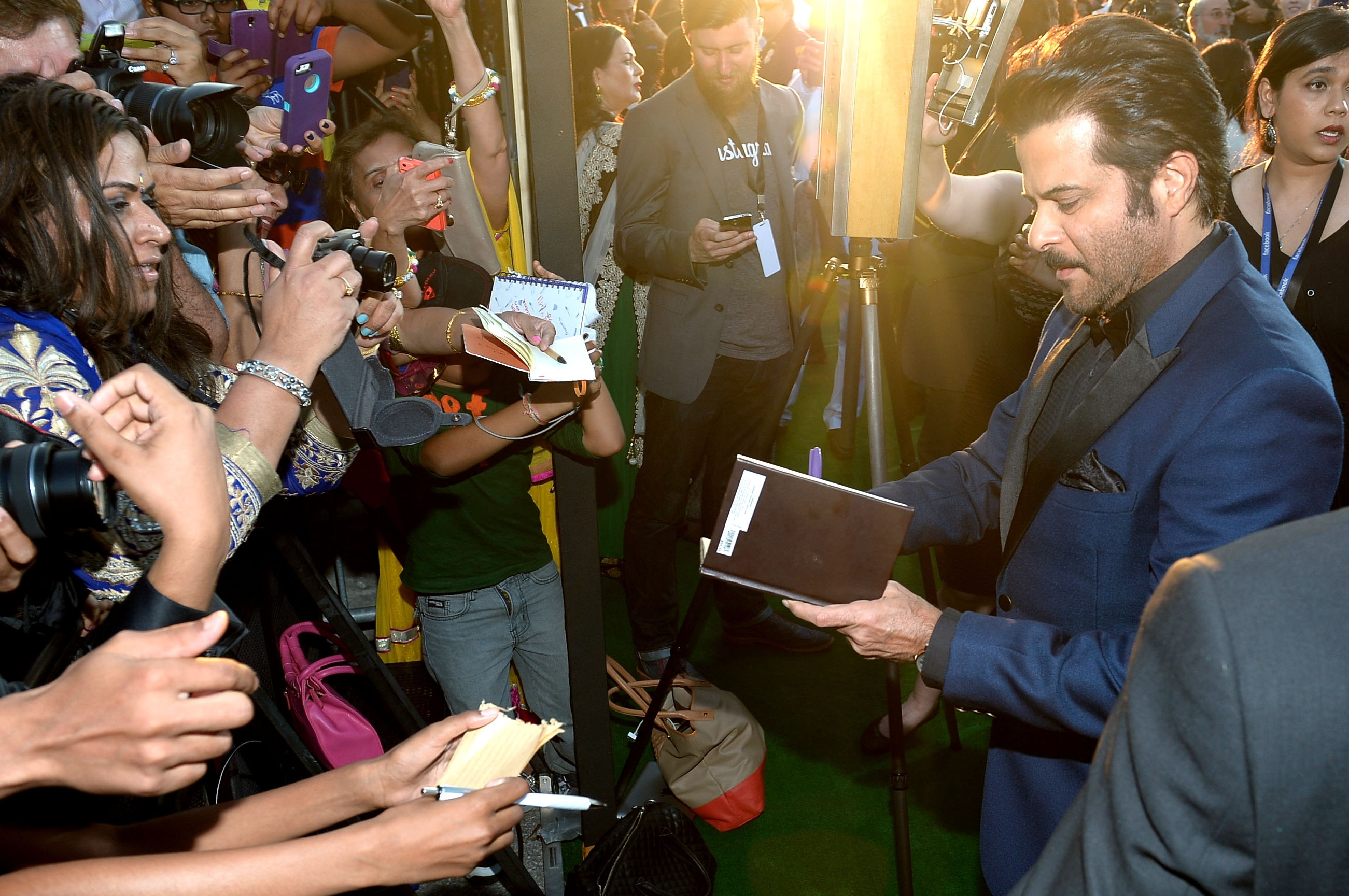 """Slum Dog Millionaire"" star Anil Kapoor signs autographs for fans before the International Indian Film Academy awards in Tampa, Fla., on Saturday."