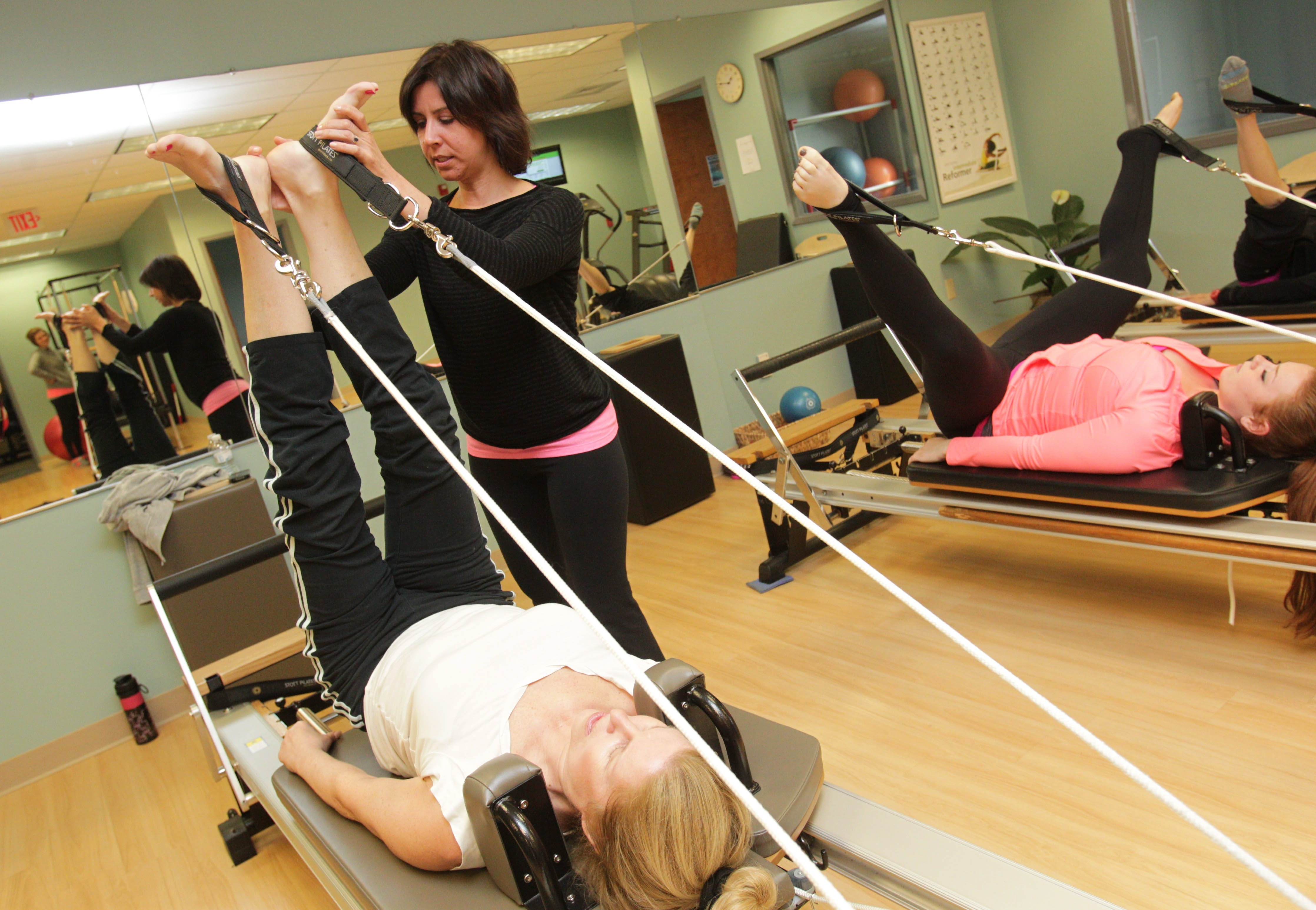 Larissa Mychaskiw, owner of Stretch Pilates & Fitness on Wehrle Drive in Williamsville, works with member Amy Pecoraro.