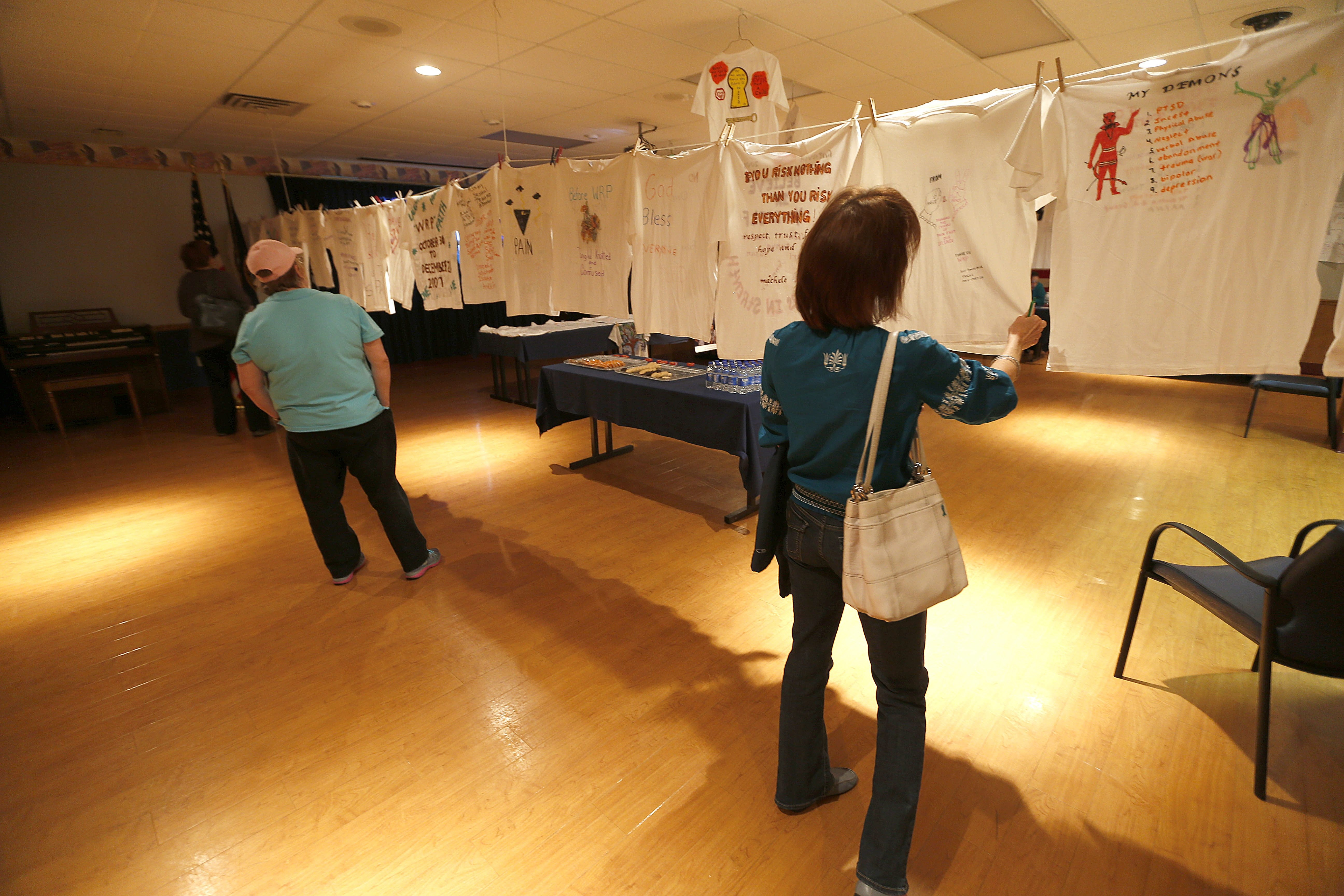 Guests and veterans, including Debbie Selkregg, of Lewiston, right, look at T-shirts decorated by victims of sexual abuse in Buffalo VA Medical Center on Wednesday.