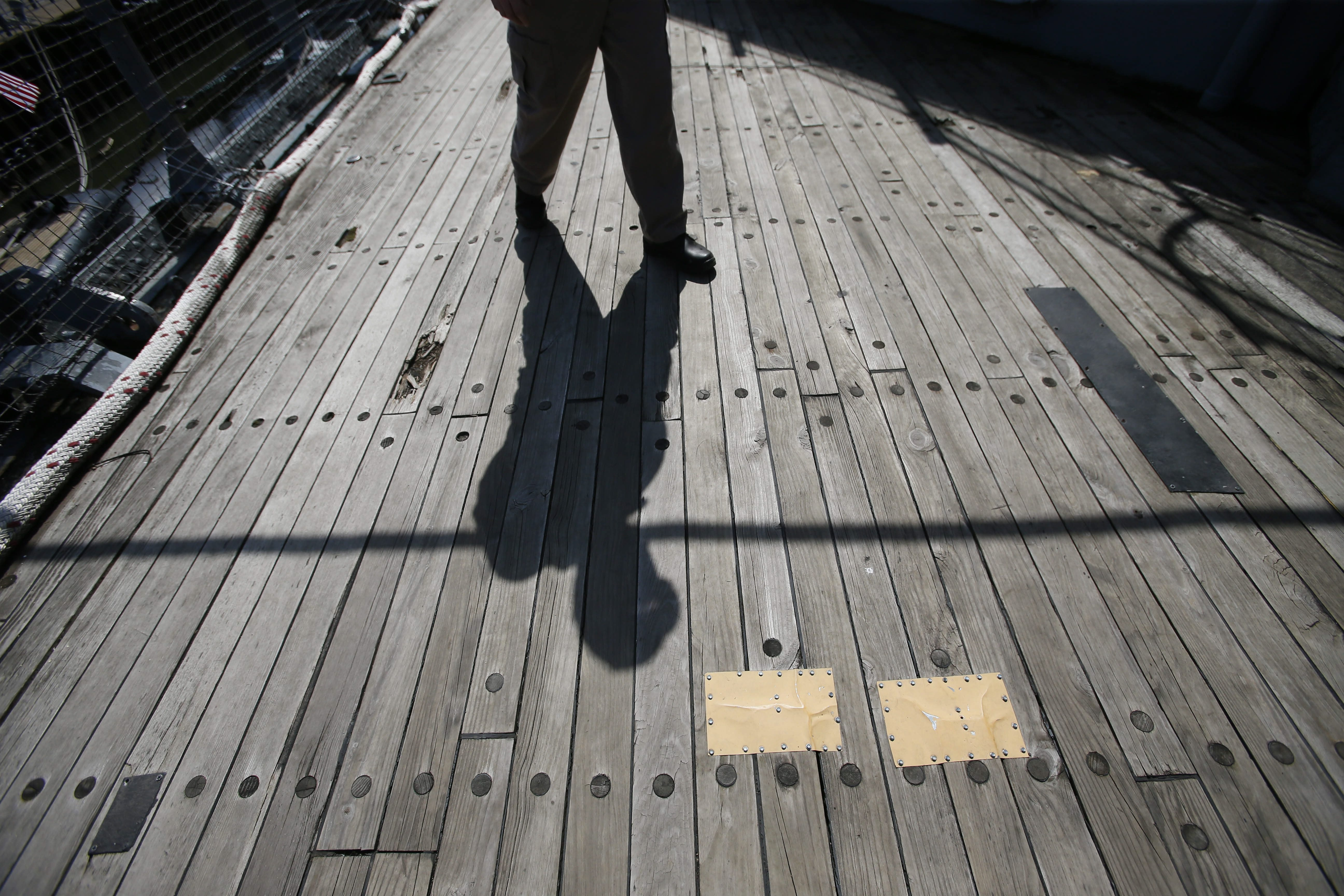 John M. Branning, superintendent of ships at the Buffalo & Erie County Naval and Military Park, casts a long shadow on the patched wooden deck of the USS Little Rock.  A fundraising effort is underway to replaced the weathered decking.