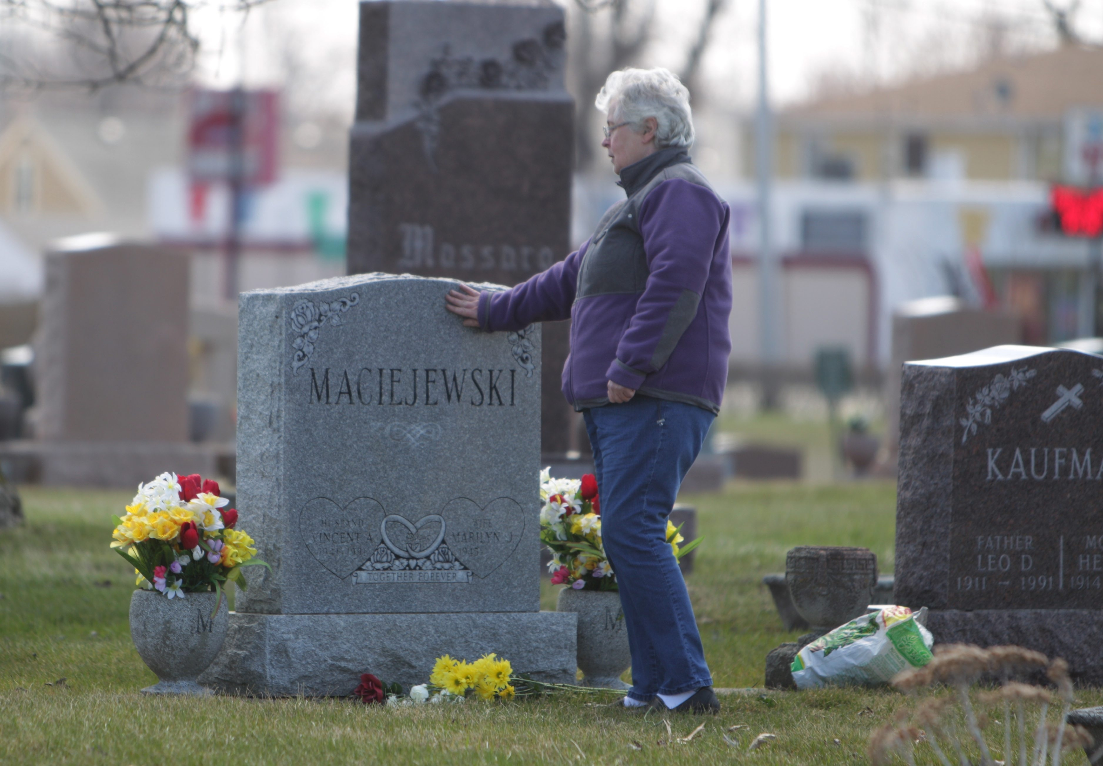 Marilyn Maciejewski touches the grave of her husband, Vincent, at Mount Calvary Cemetery on Saturday. Maciejewski also visited the graves of her brother and parents to commemorate the Easter holiday.