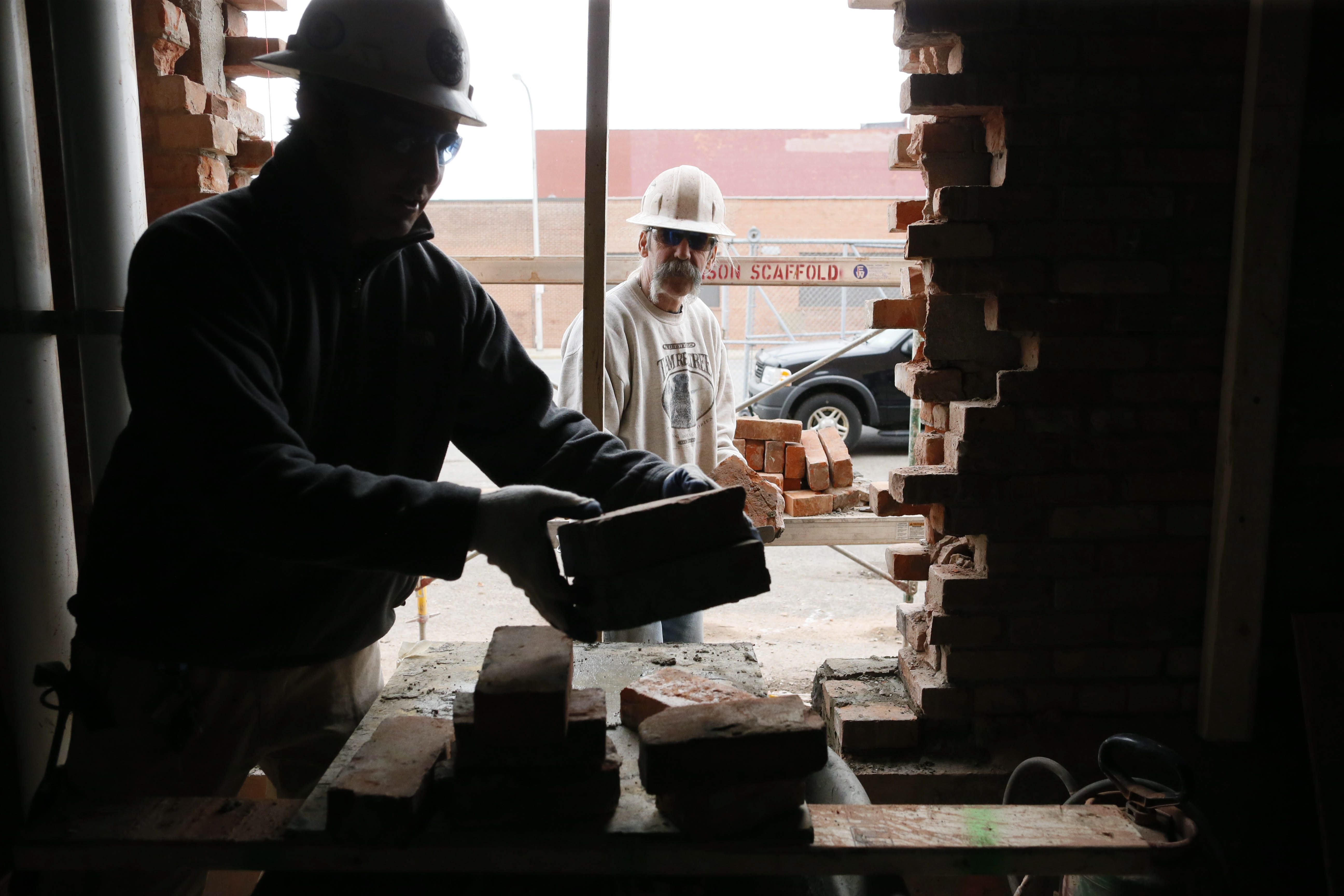 Masons Jay Poleszak, left, and Butch Kozma of Abraxis Masonry Restoration repair a brick wall at the former Planing Mill at 141 Elm St. that is under redevelopment into 22 apartments by TM Montante.