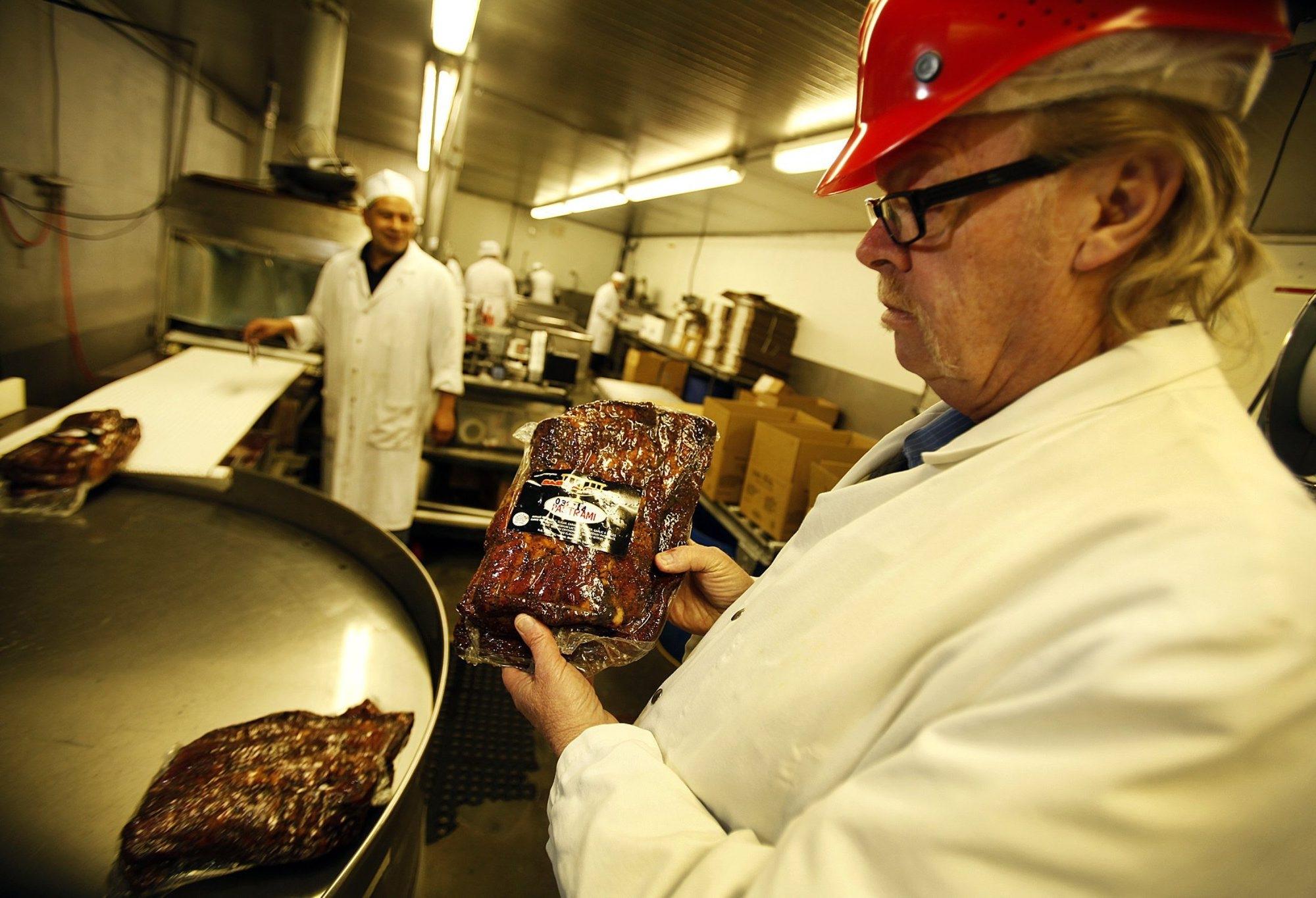Jerry Haines, right, general manager at R.C. Provisions in Burbank, Calif., checks packaged pastrami ready for shipping. Beef prices are at record highs because of thinning cattle herds devastated by drought, and the soaring cost of raw materials has driven profit margins down.