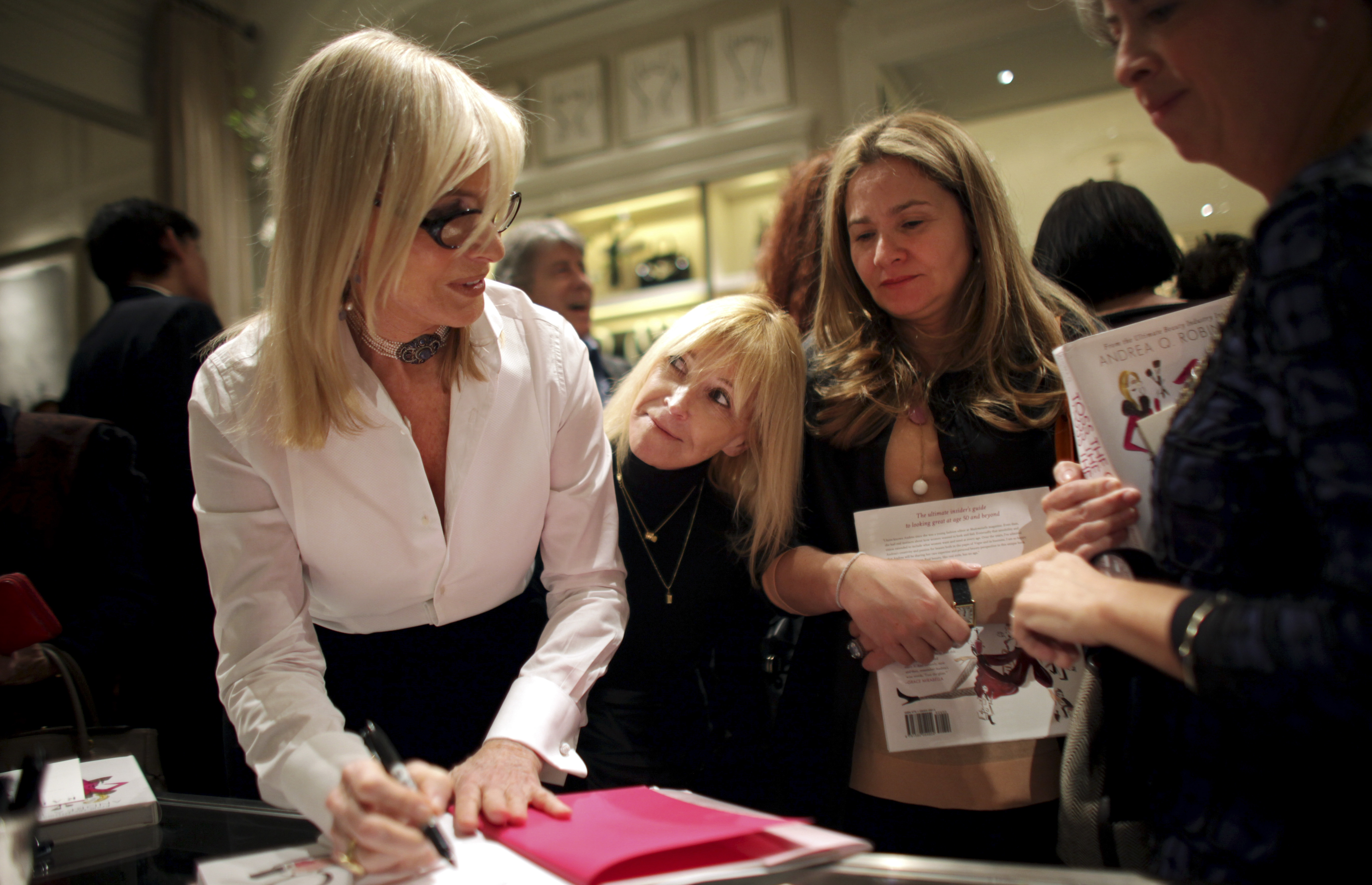 """Andrea Robinson, a cosmetics industry veteran, signs copies of her new book, """"Toss the Gloss: Beauty Tips, Tricks and Truths for Women 50+,"""" during a party earlier this month in New York."""