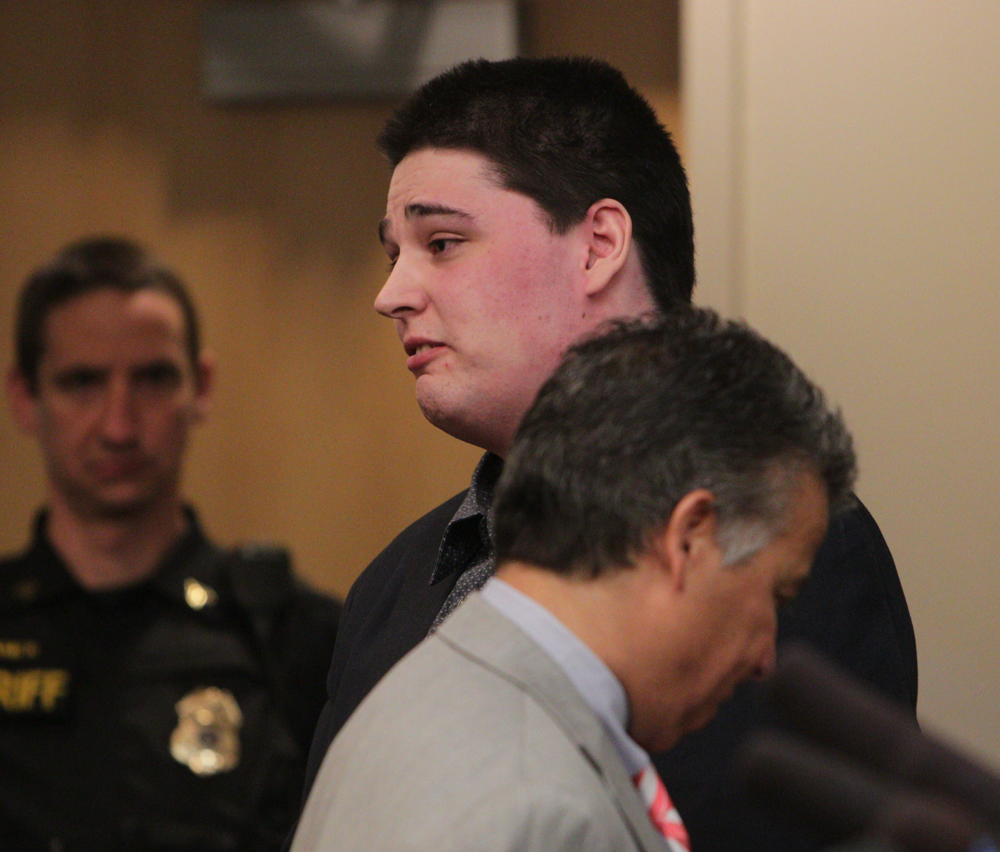 Cody Testerman, 23, addresses his family in court after he was sentenced to 25 years for killing his half brother Jesse Seneca in 2012. In the foreground is his lawyer Andrew LoTempio.