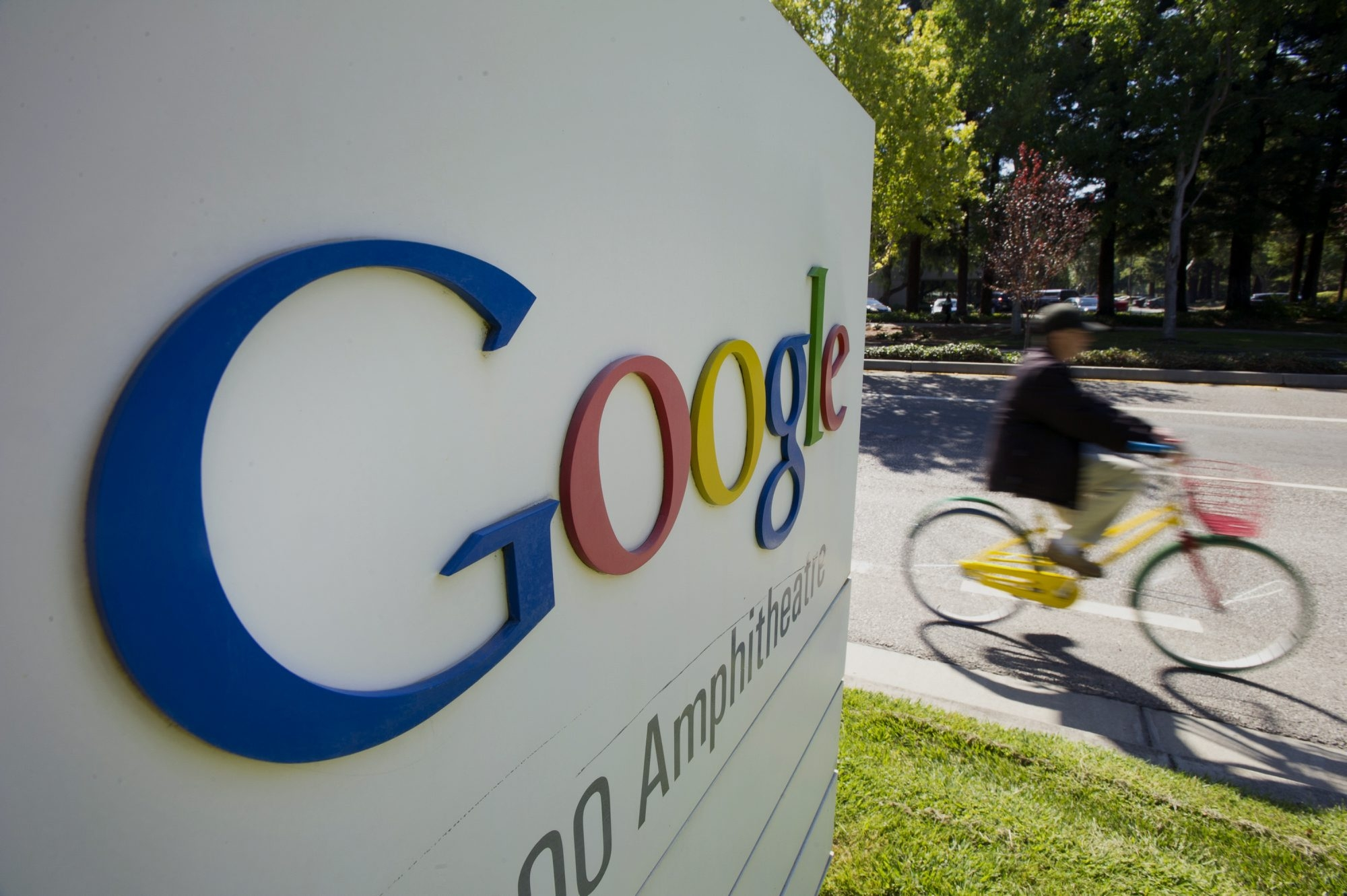 A bicyclist rides his bike past a Google Inc. sign in front of the company's headquarters in Mountain View, California, U.S., on Friday, Sept. 27, 2013. Google is celebrating its 15th anniversary as the company reaches $290 billion market value. Photographer: David Paul Morris/Bloomberg
