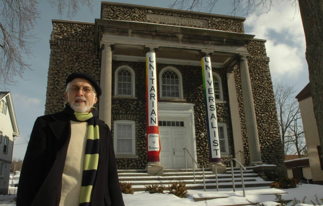 Tom Yots, shown in a Buffalo News file photo standing in front of the Unitarian Universalist Church Niagara Falls, will retire July 1 as executive director of Preservation Buffalo Niagara.