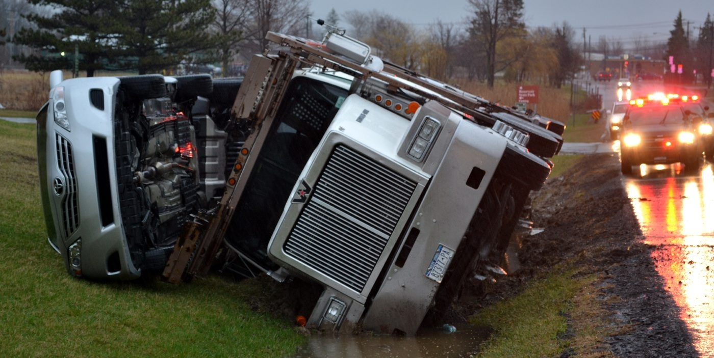 A transport truck loaded with cars overturned and rolled into a ditch on Route 31 this morning.