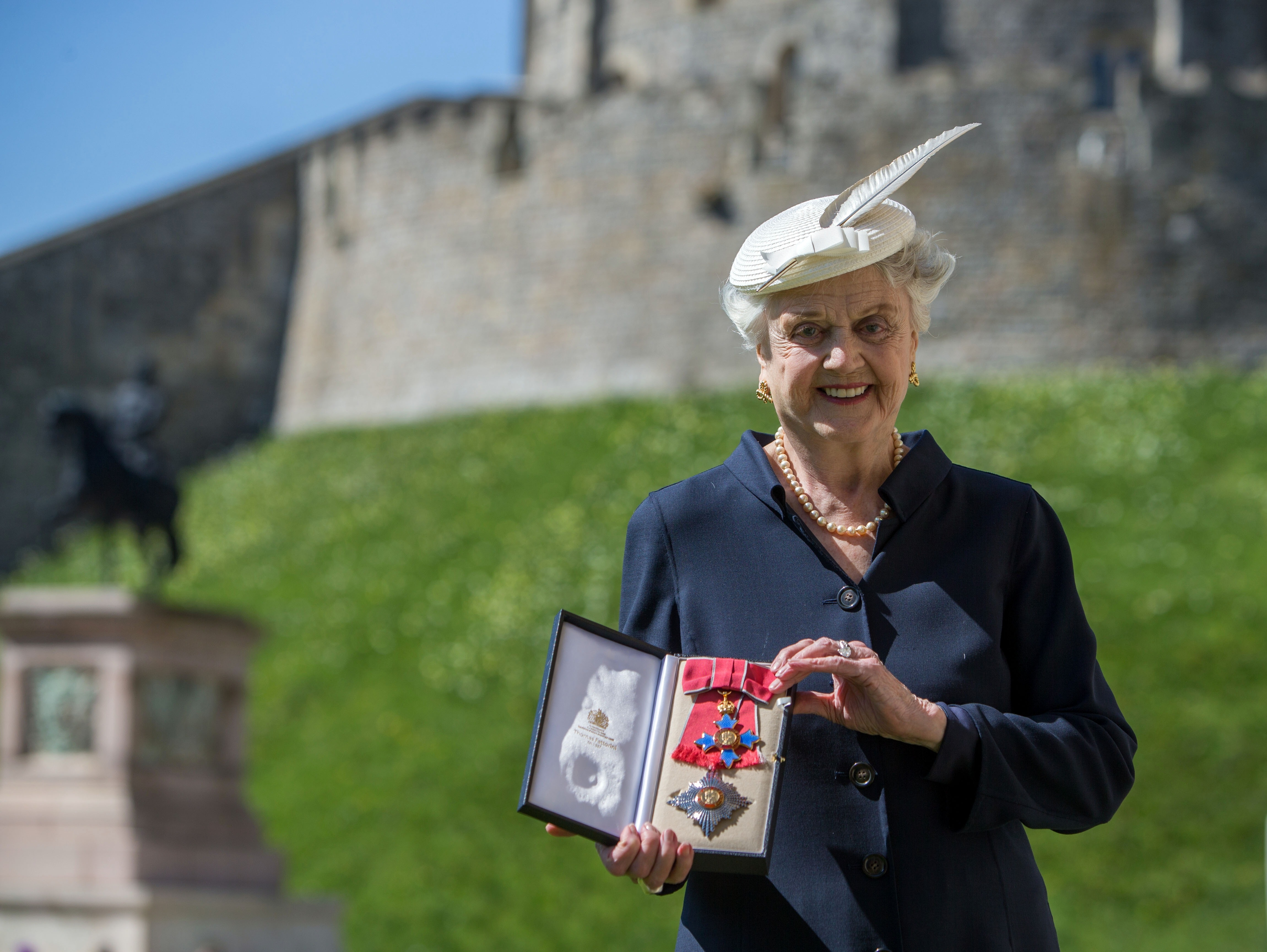 One heck of a dame: Actress Angela Lansbury poses with her Dame Commander medal given to her by Queen Elizabeth II at an Investiture ceremony at Windsor Castle on Tuesday.
