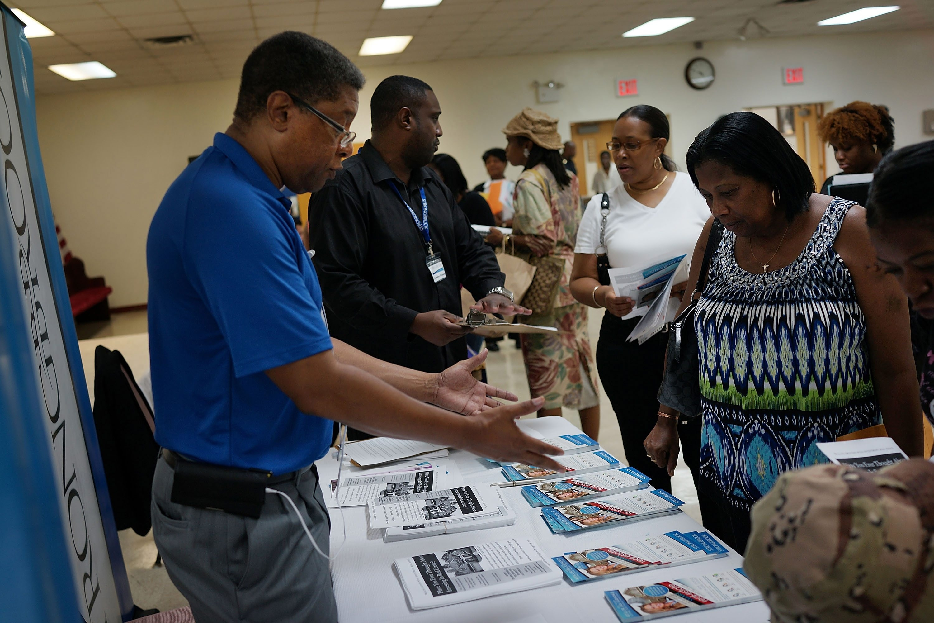 Job seekers talk to recruiters at a job fair in Clinton Hill, Brooklyn, on Aug. 28. Job hunters should know that legitimate headhunters are paid by employers, not by those seeking employment.