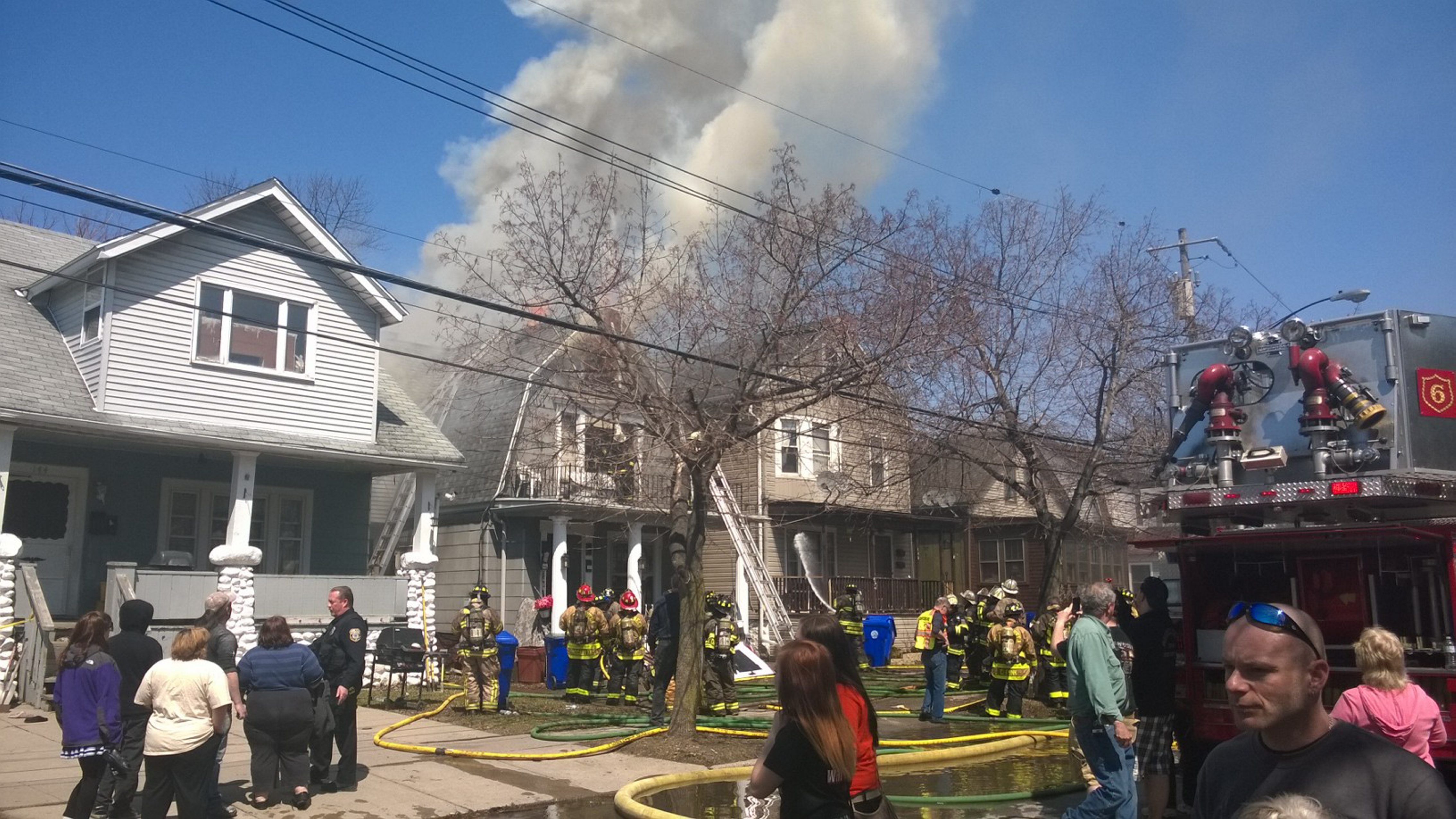 Flames shoot from the roof of a burning home on Burch Avenue in West Seneca Saturday.