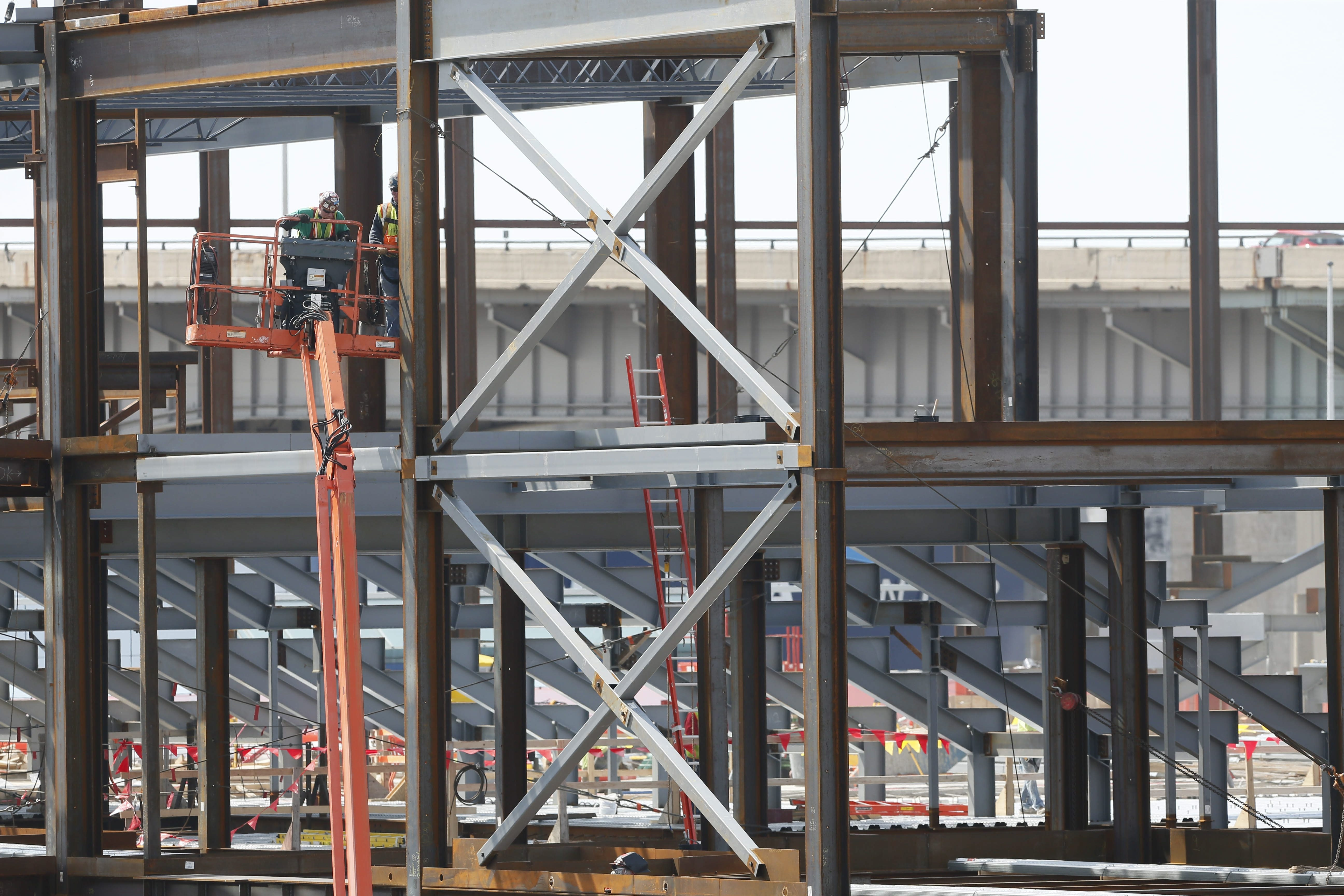 Workmen are setting the framework of a hockey rink six stories above the ground, racing an October deadline.