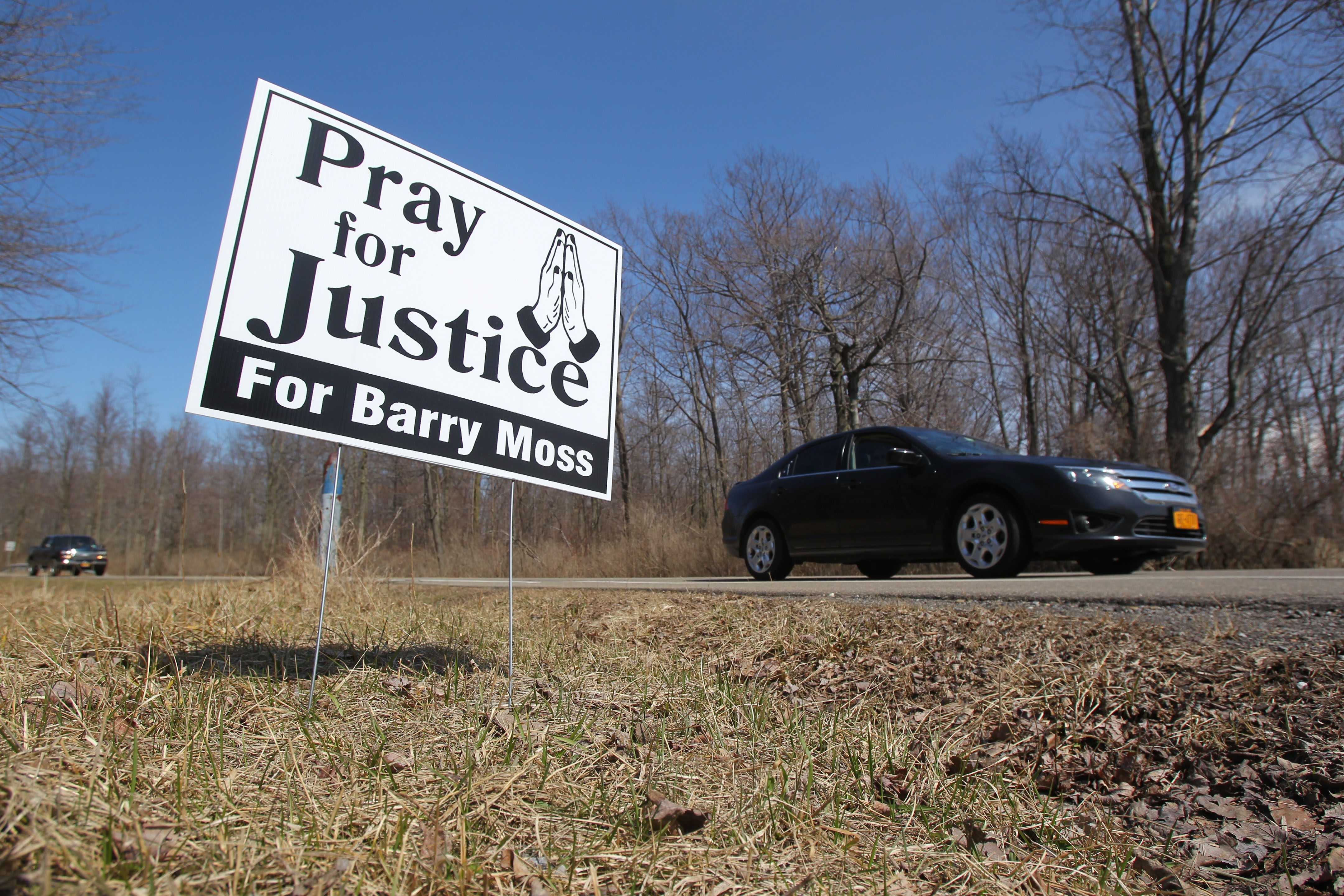 Some 150 signs seeking justice for the death of Barry Moss have sprung up in Evans.