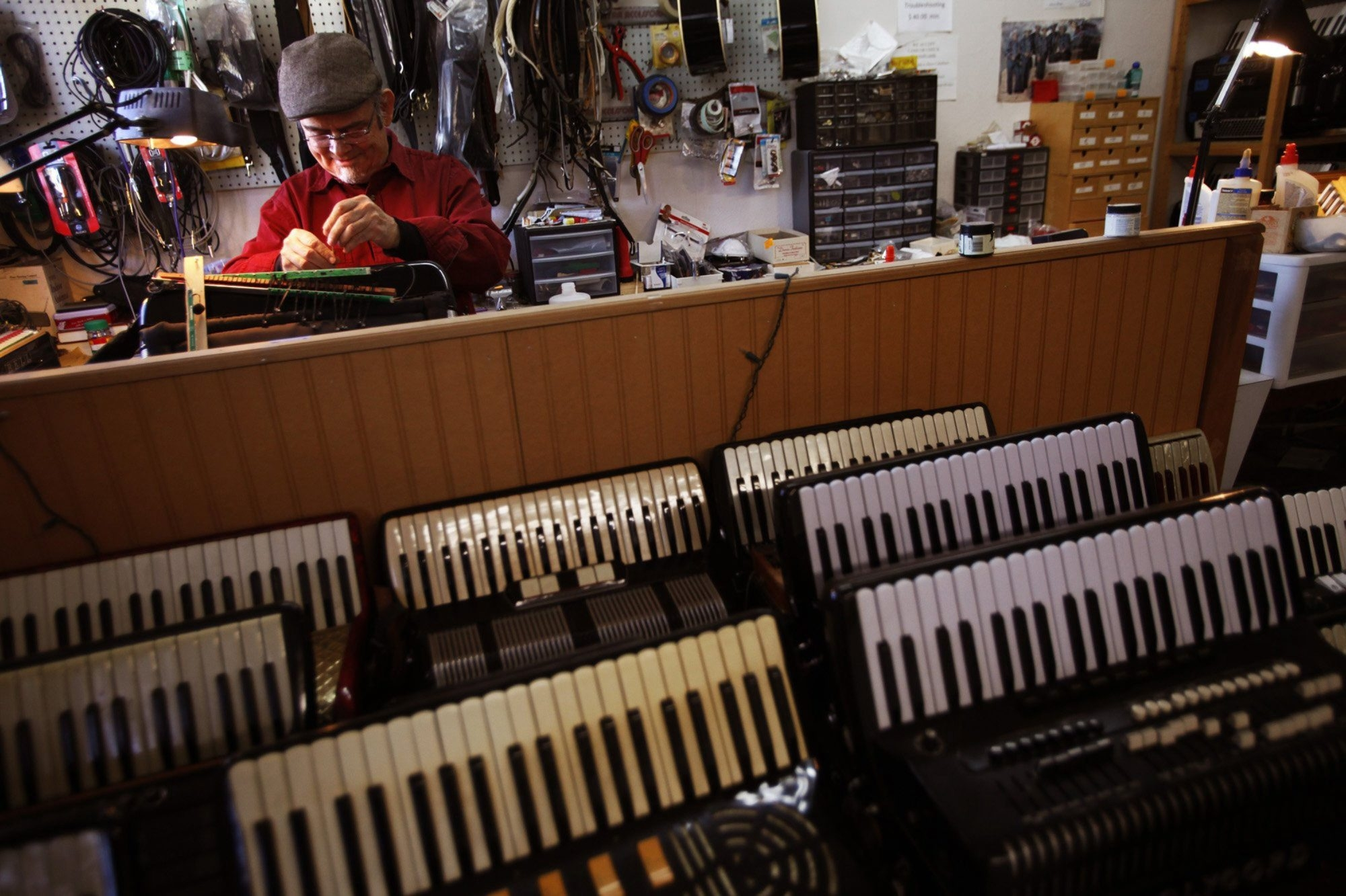 Dave Caballero, 68, repairs an accordion at Dave's Accordion School, one of the only remaining places in Los Angeles where people can learn to play or get their accordions fixed.