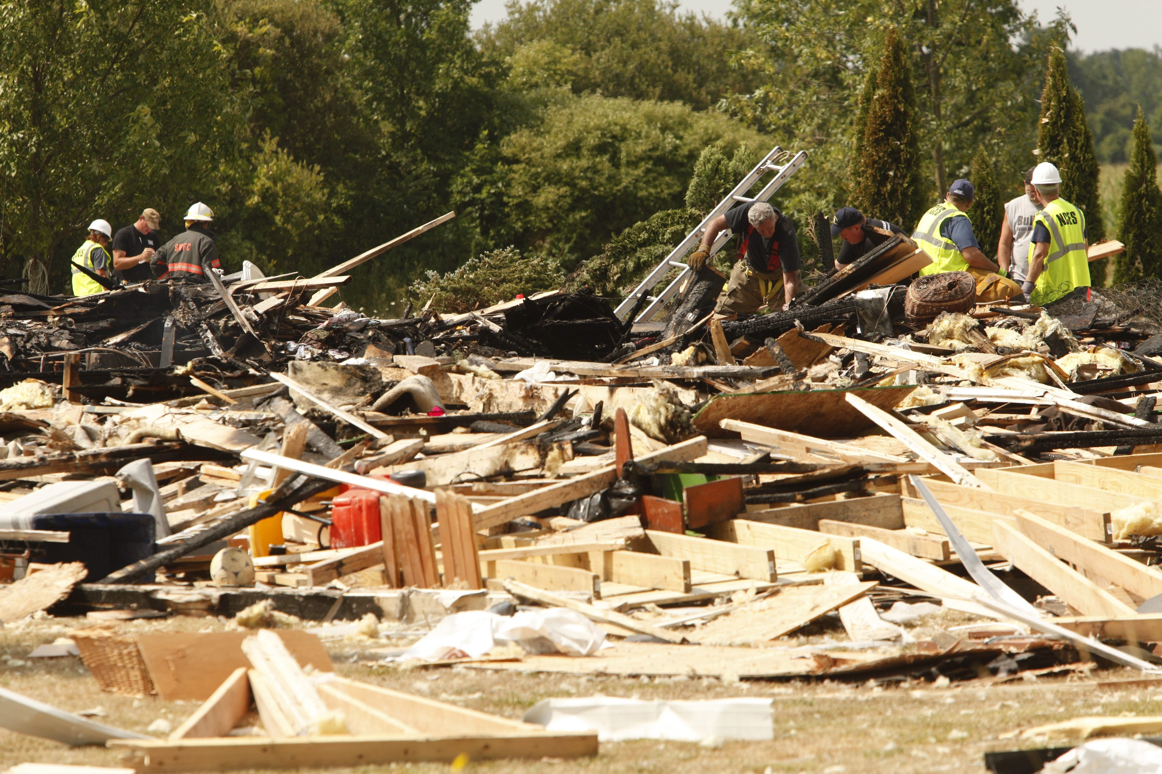 Police and fire officials investigate the scene of an explosion that killed Sarah Johnson, 14, and seriously injured four family members on Chestnut Road in Wilson, on July 24, 2012.