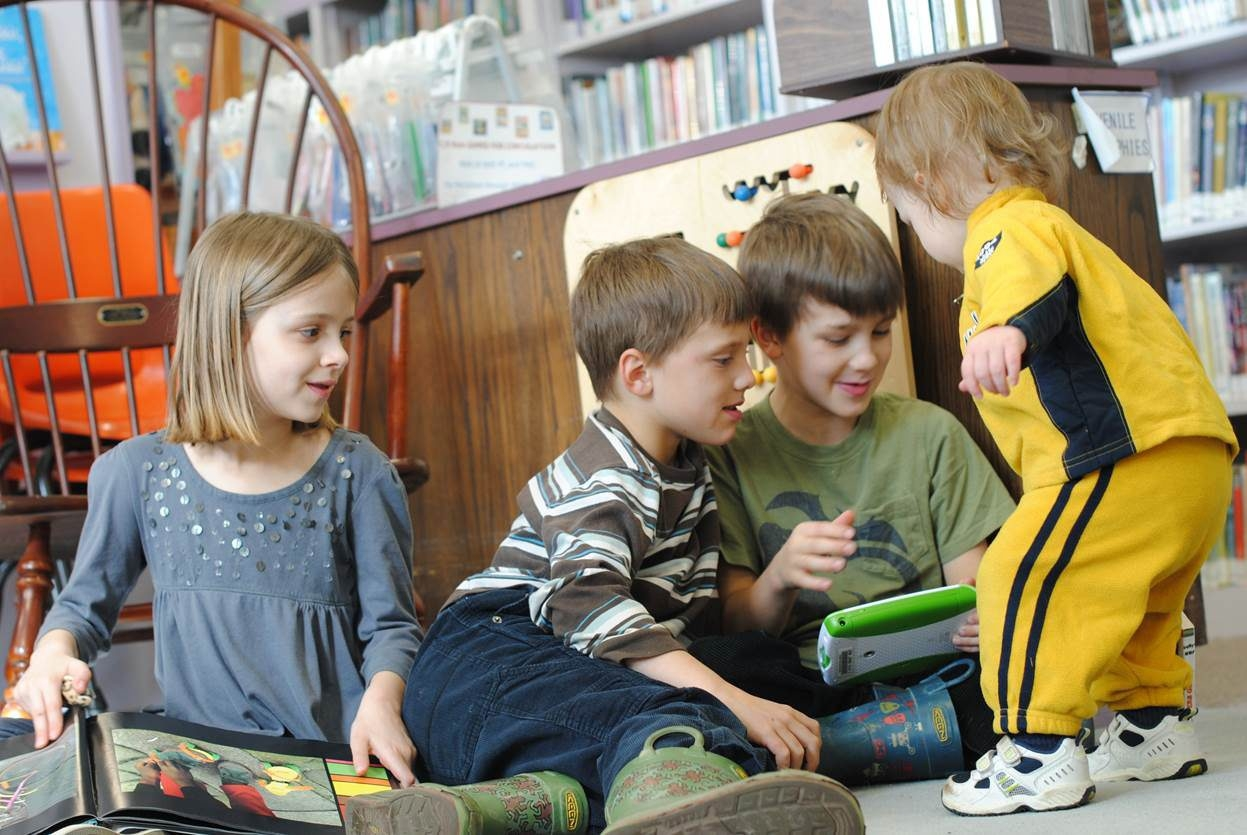 From left, Anna Lauger, Leo Clark, Oliver Clark and Atticus Clark check out the Youngstown Free Library.