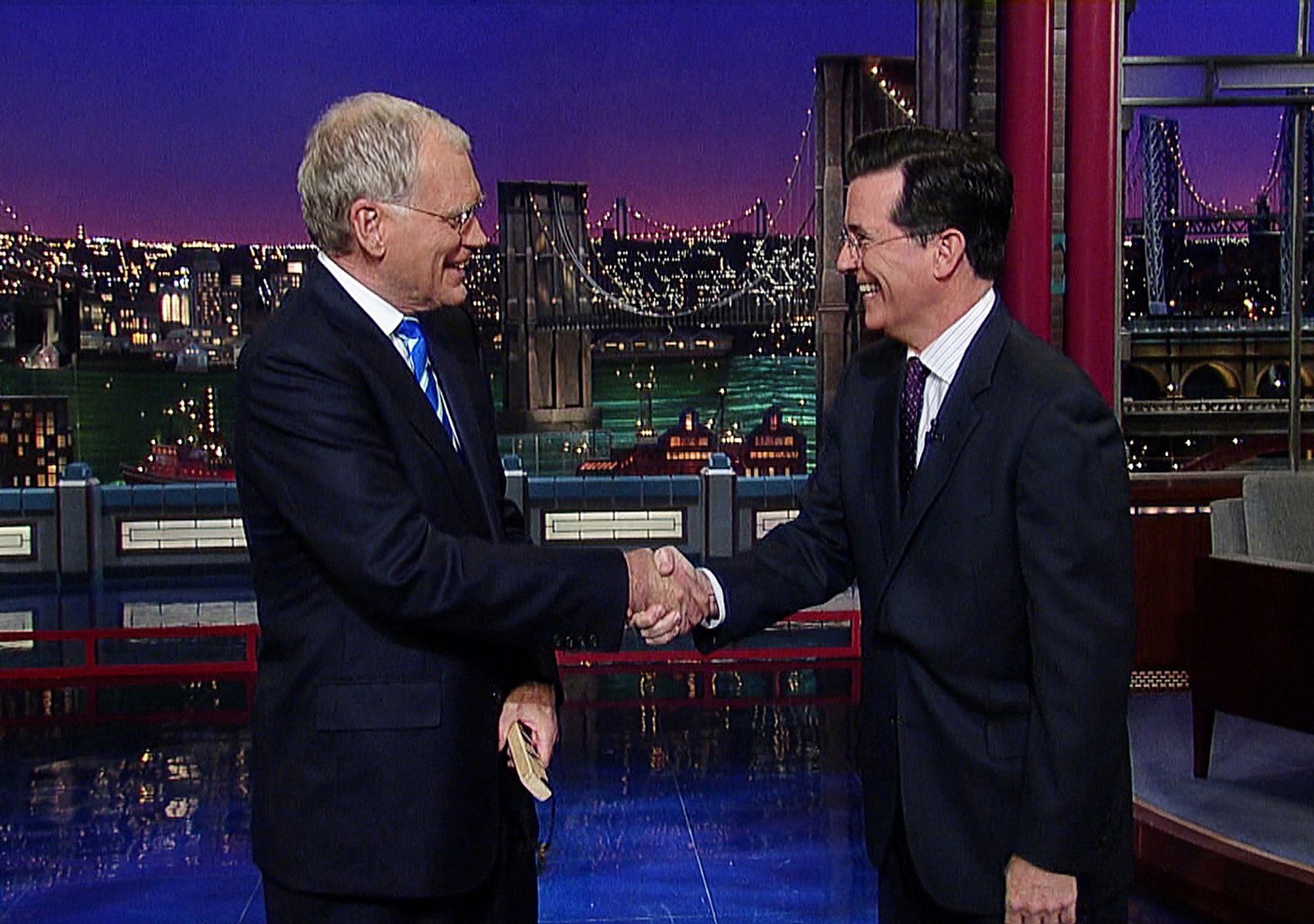 """This May 4, 2011, image from video released by CBS shows host David Letterman, left, shaking hands with fellow talk show host Stephen Colbert of """"The Colbert Report,"""" during a surprise visit on the """"Late Show with David Letterman,"""" in New York."""