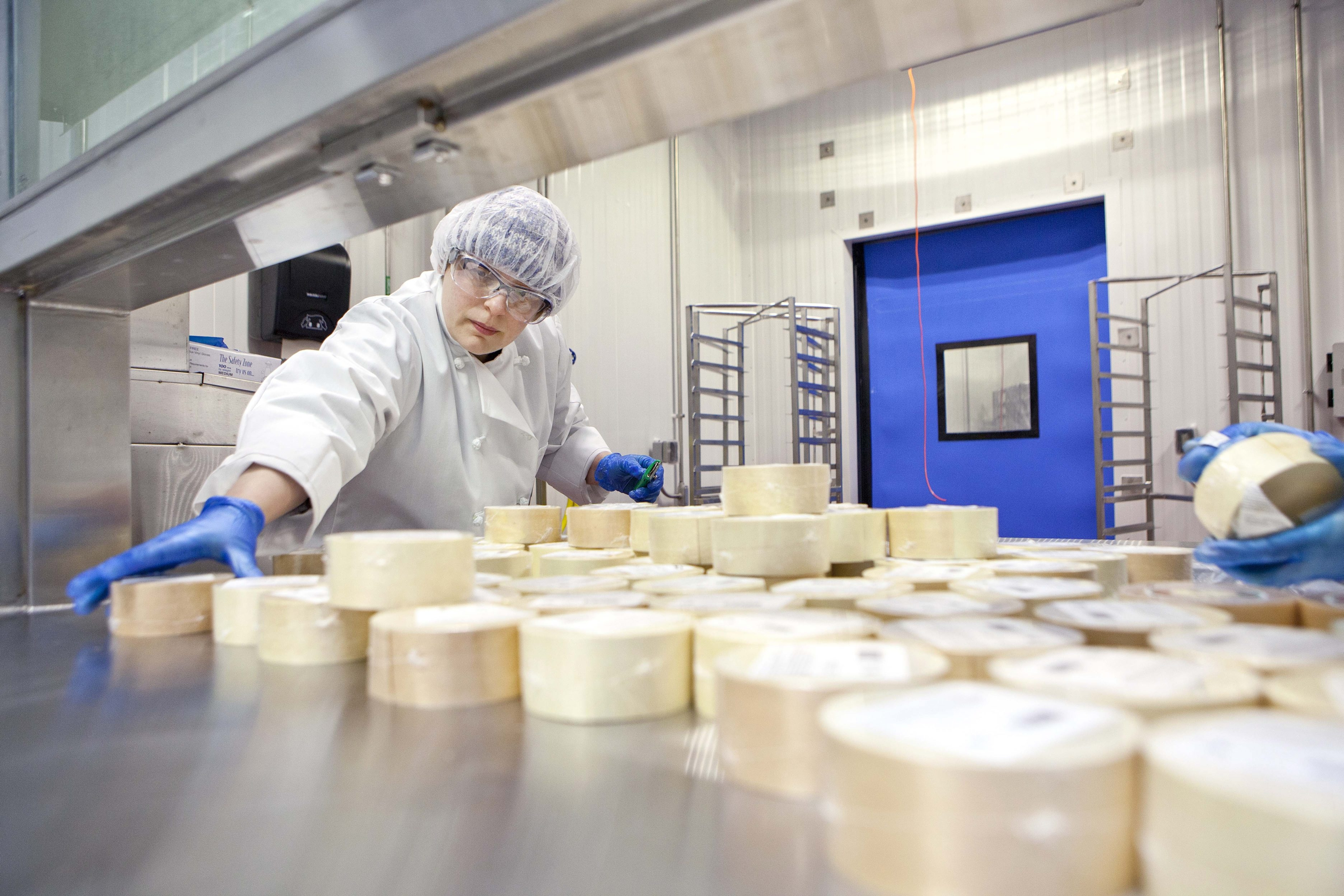 A cheese worker prepares to load new cheese into the cheese cave.