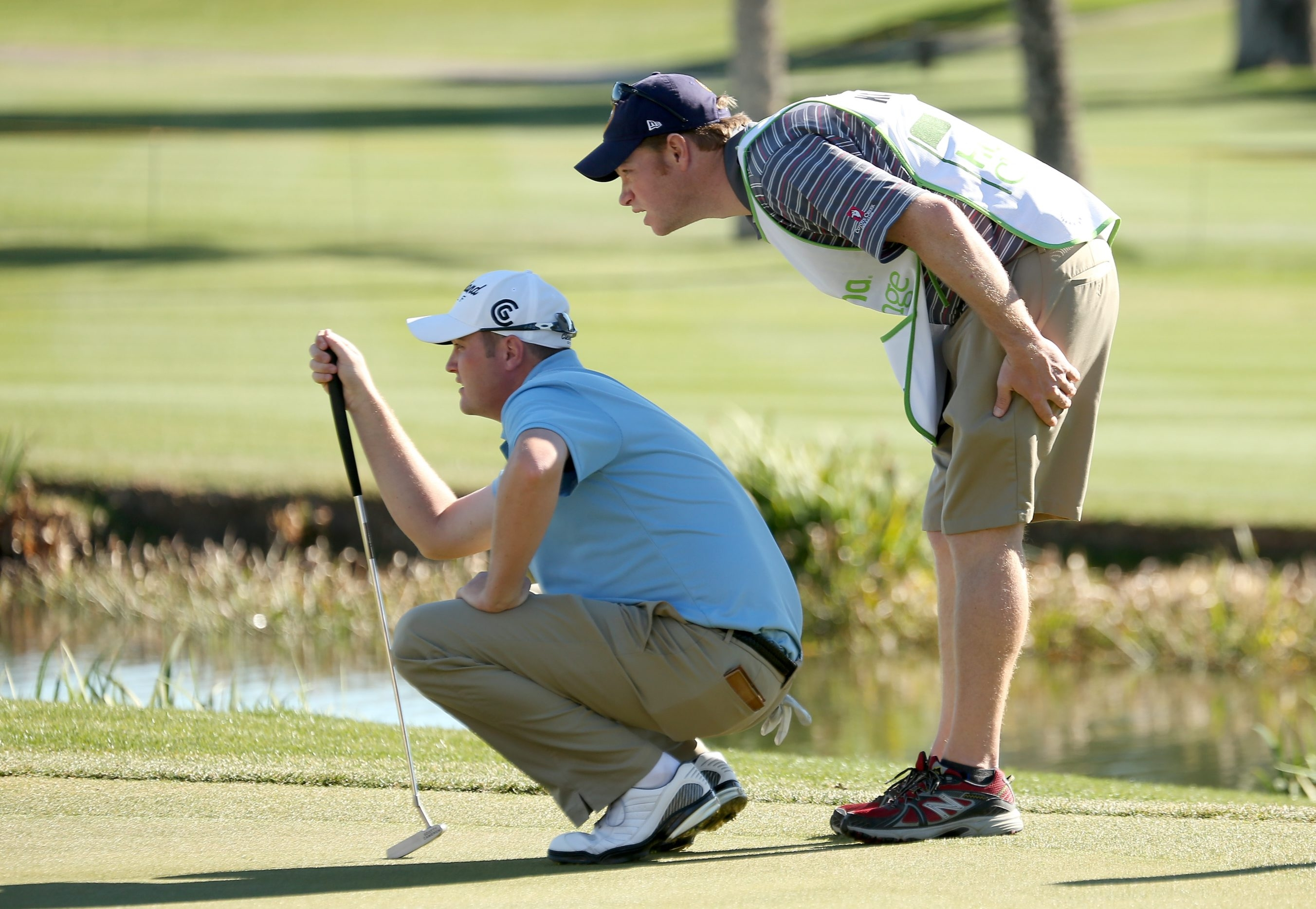 Caddie Aaron Alpern of Buffalo, right, helps PGA Tour pro Jason Kokrak line up a putt at the Humana Challenge in January 2013.