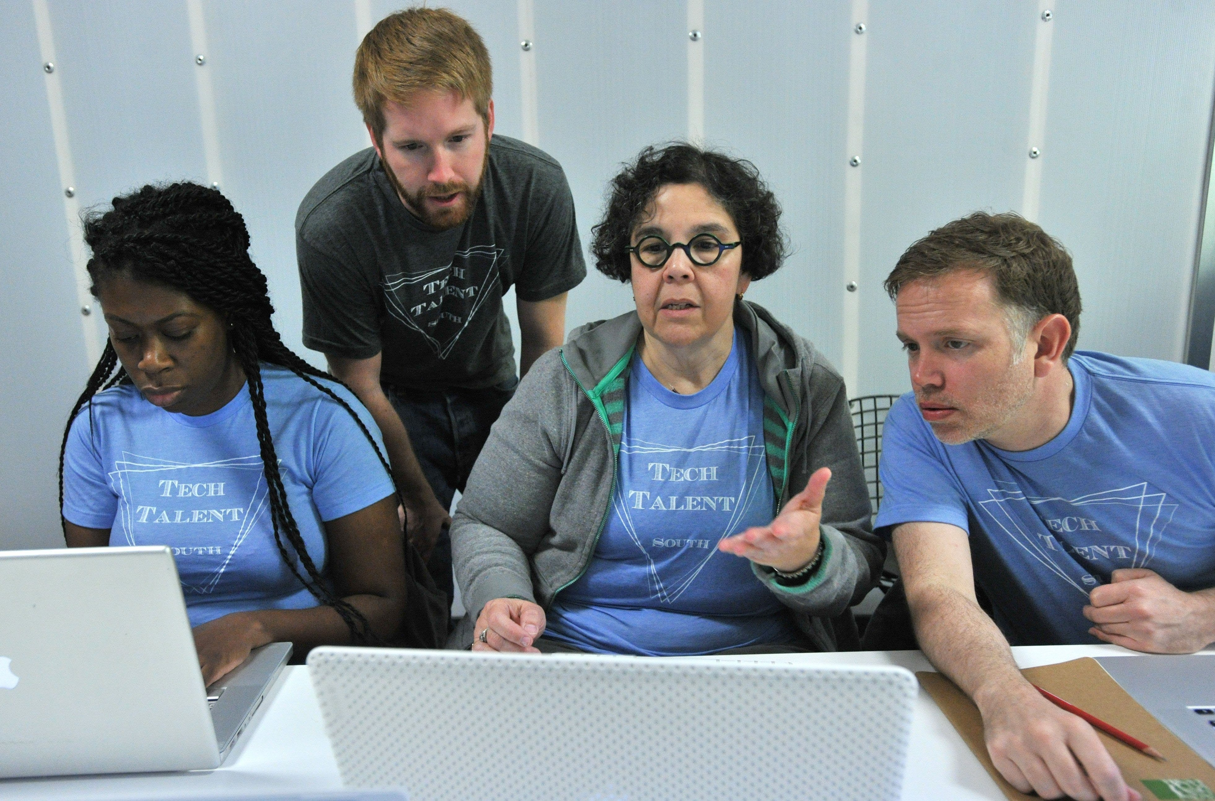 Richard Simms, standing, a co-founder of Tech Talent South, helps student Odette Colon, center, as other students Tammy Bowen, left, and Todd Brunsvold work on their project during Development Boot Camp at Tech Talent South in Old Fourth Ward on Feb. 26 in Atlanta.