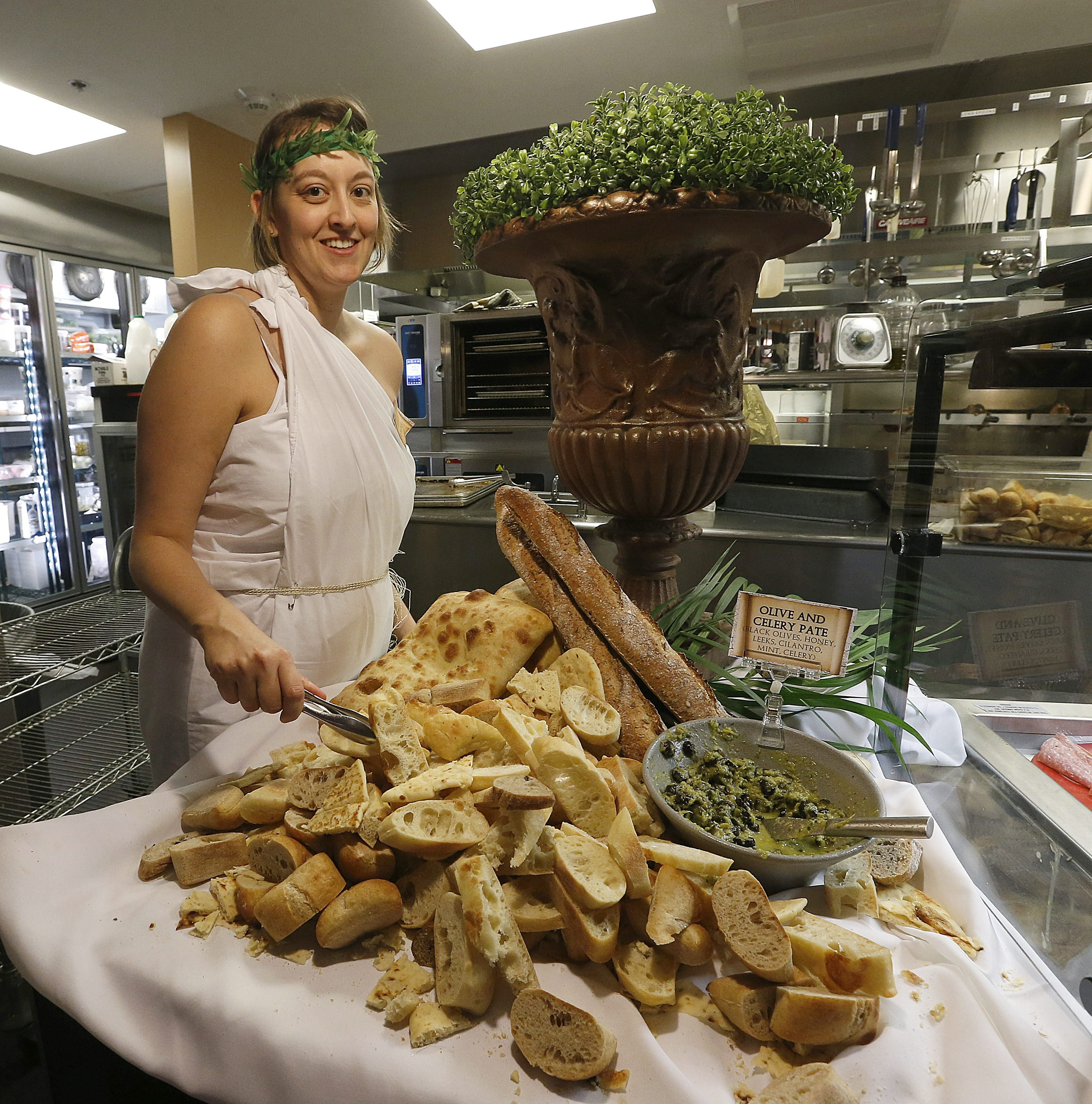 """General manager Lauren Brantley prepares the bread station before the """"Eat Like a Roman"""" dinner in the Crossroads Culinary Center of Red Jacket Quad on UB's North Campus Sunday."""