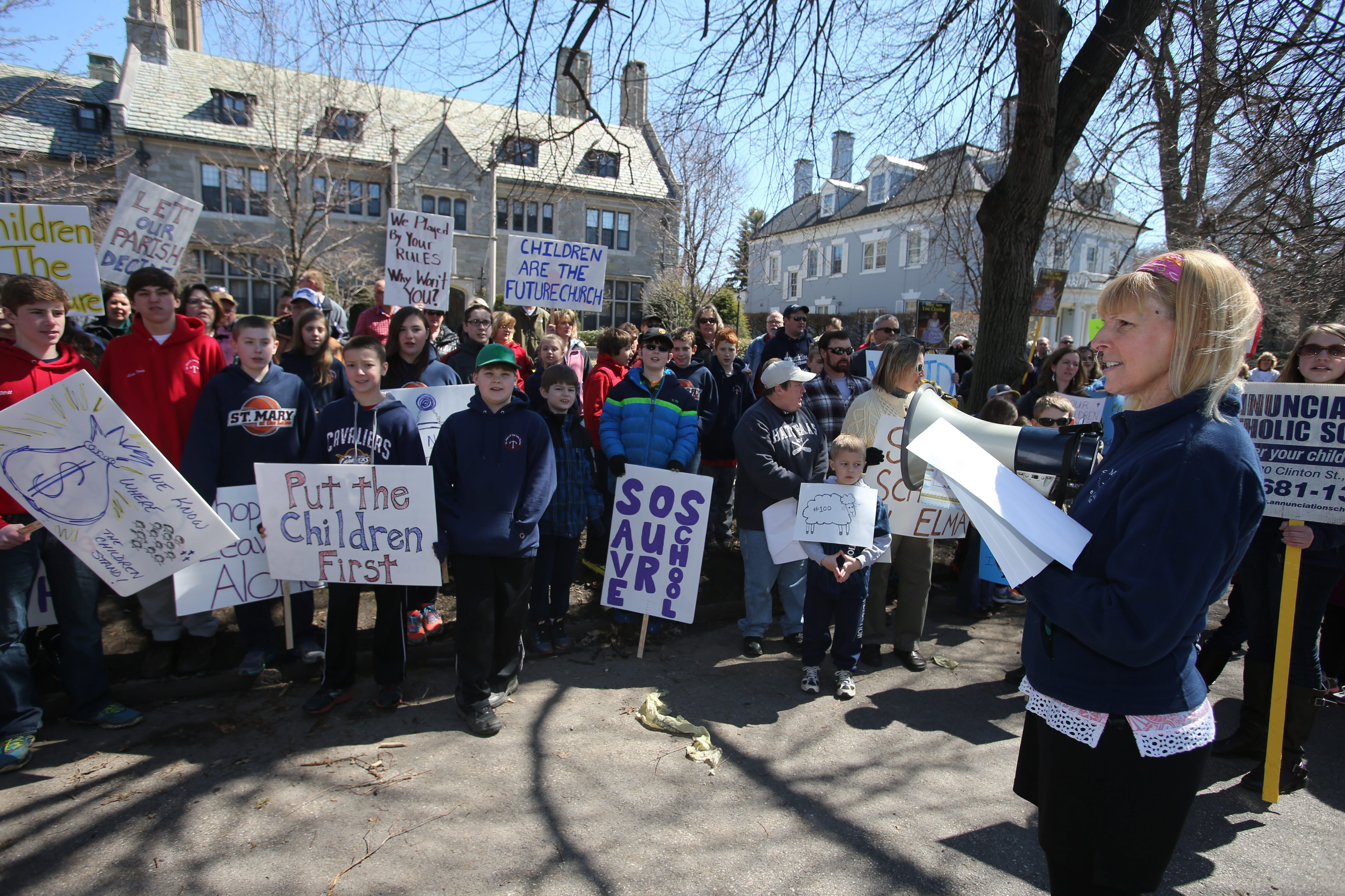 Chris Herzog, foreground, of St. Mary of the Lake Parish in Hamburg, leads about 120 protesters outside Bishop Richard J. Malone's mansion on Oakland Place in Buffalo as the diocese is taken to task for not letting parishioners have enough input on school closures.