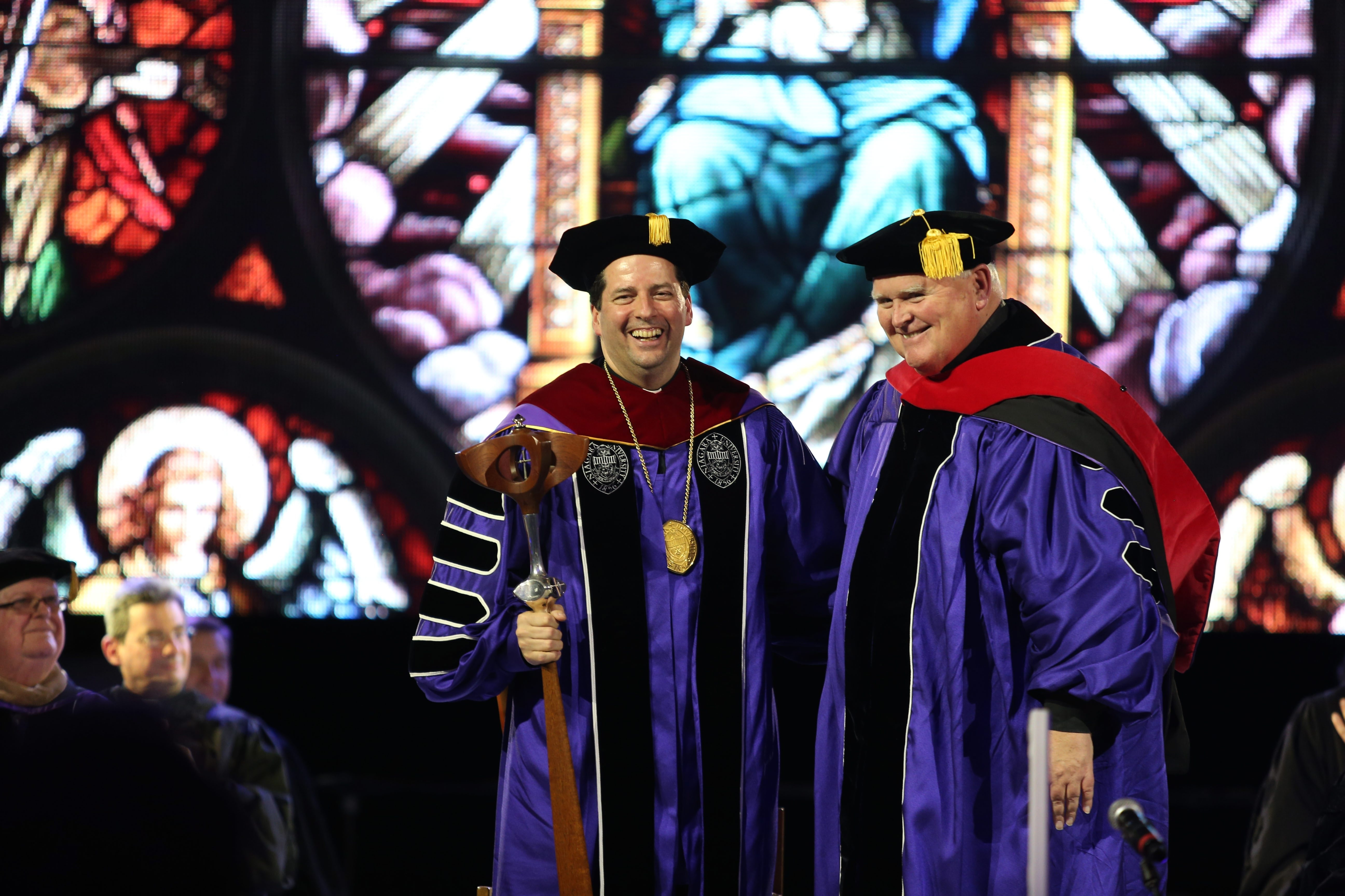 The Rev. Michael J. Carroll, right, smiles along with the Rev. James J. Maher after presenting him the mace during his inauguration as the 26th president of Niagara University in the Gallagher Center on the school's Lewiston campus Friday.