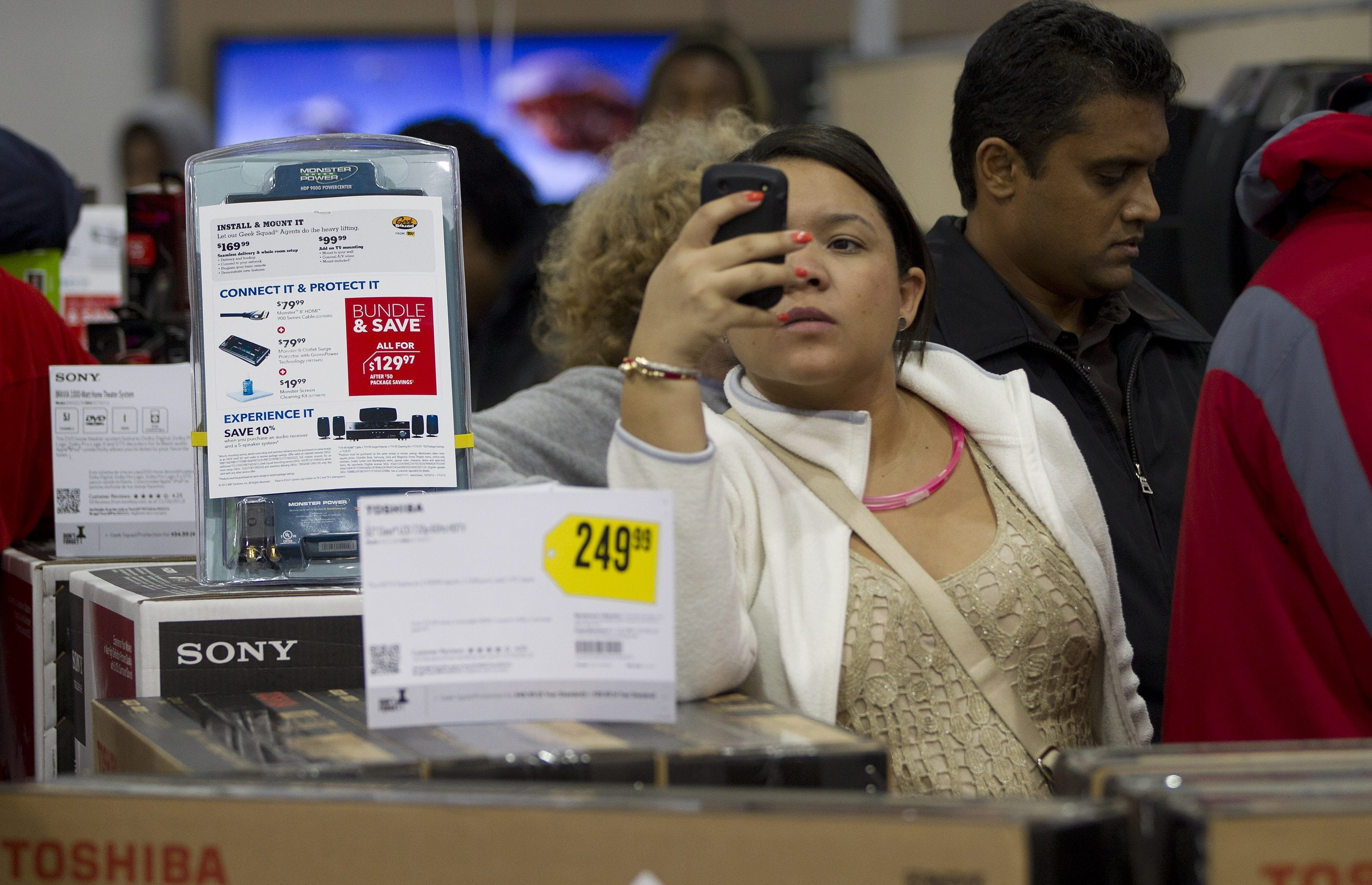 A shopper uses her smartphone to shop for bargains.