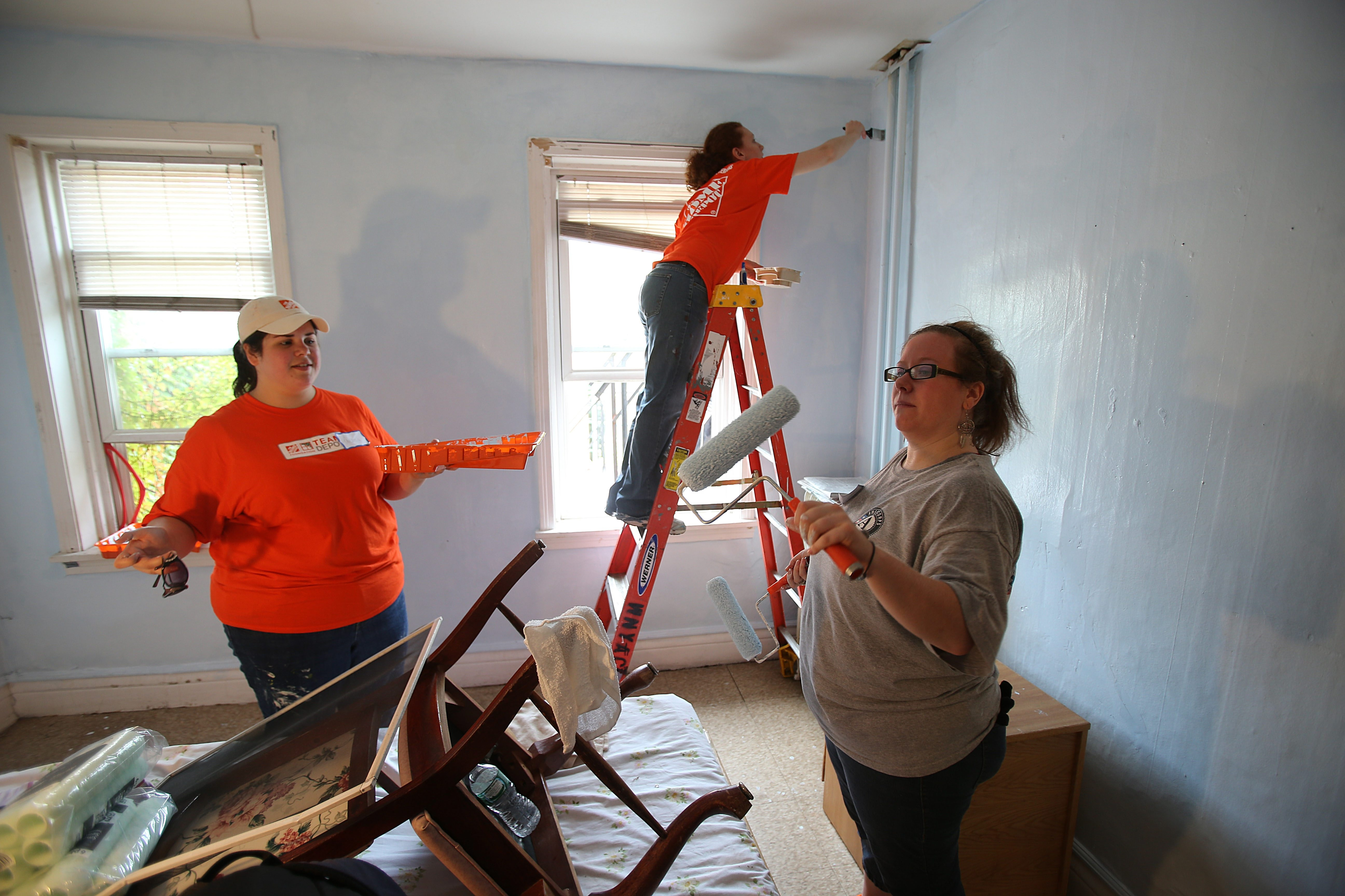 Volunteers, from left, Theresa Ziegler, Celeste Elliott and Megan Bingham, paint a room last September in Buffalo.