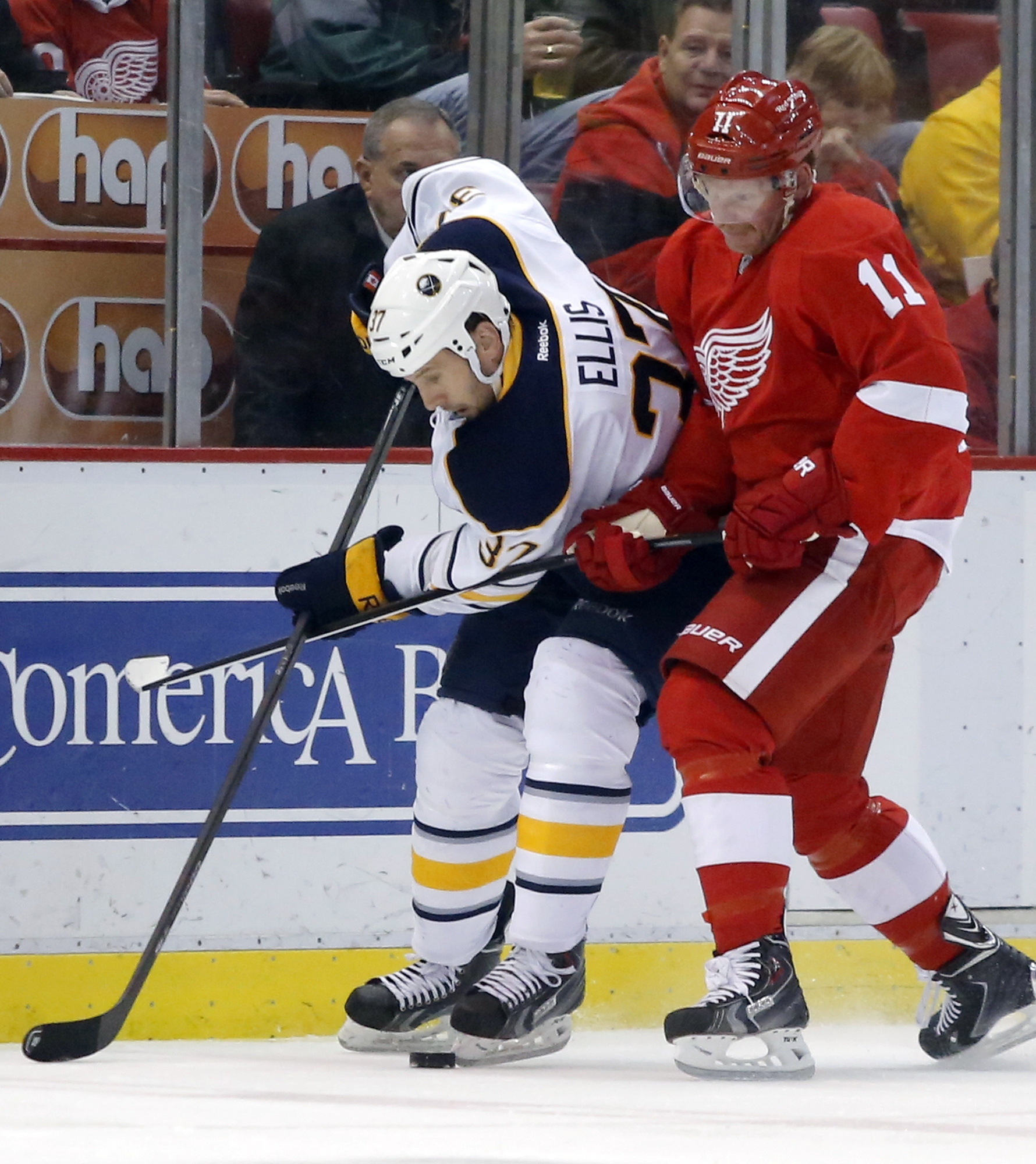 Buffalo's Matt Ellis battles Detroit's Daniel Alfredsson for a loose puck during the Red Wings' 3-2 win.