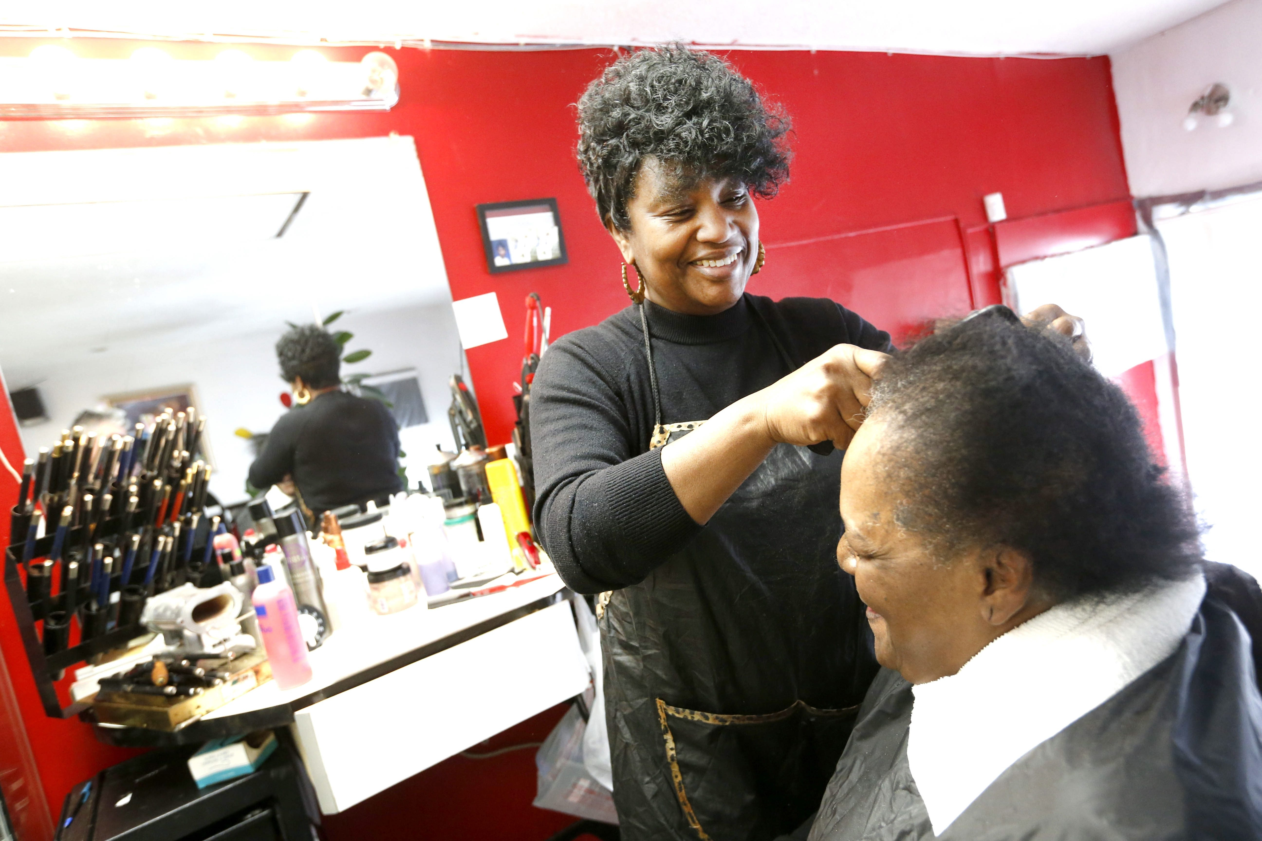 Sheila Banks Clency, owner of Crowns of Glory hair salon on Bailey Avenue, takes care of customer Viola Atkinson on Thursday.