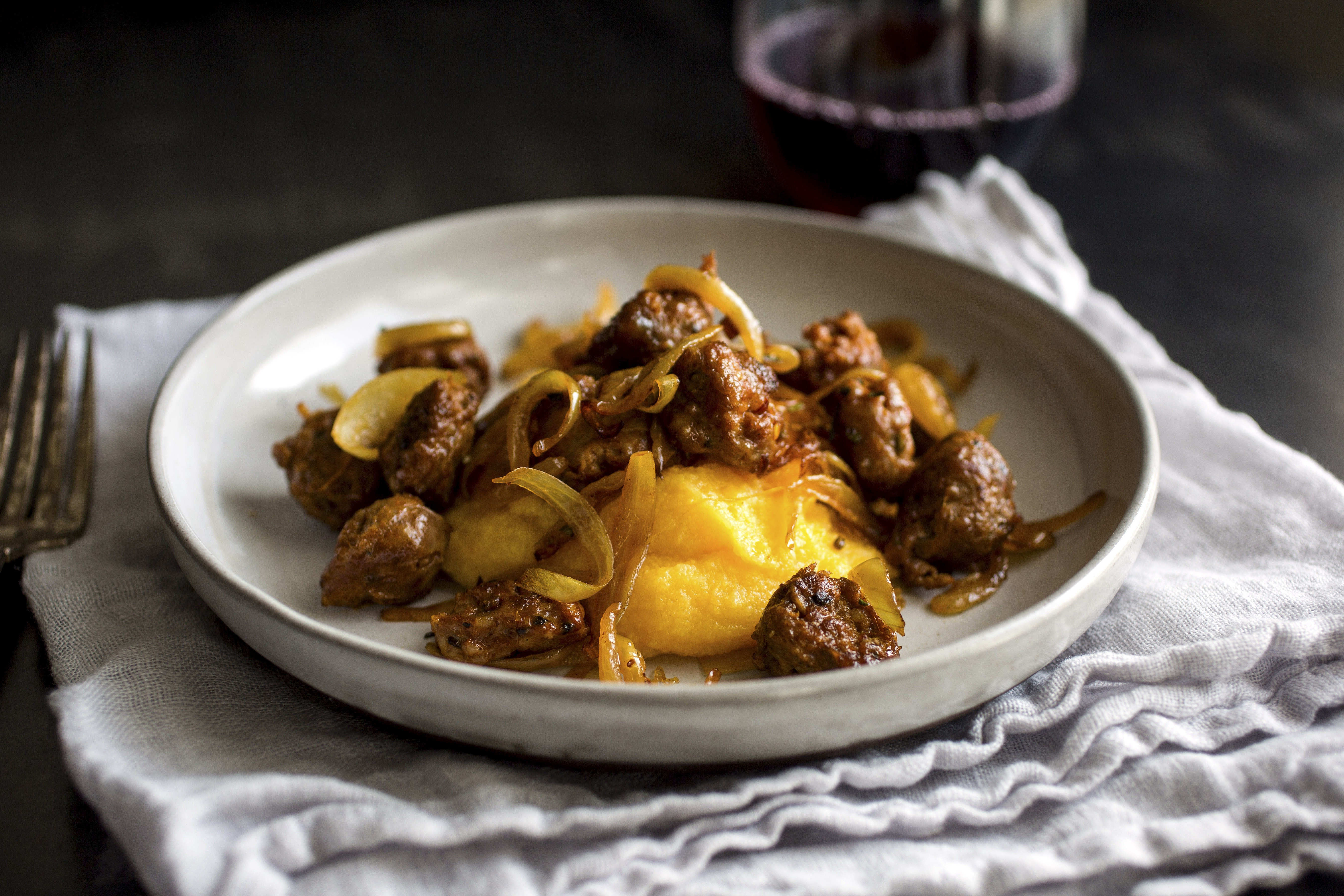 No longer a pricey novelty for gourmets, polenta is widely available and makes a fine base for an improvised after-work meal like this butternut squash polenta with sausage and onion.