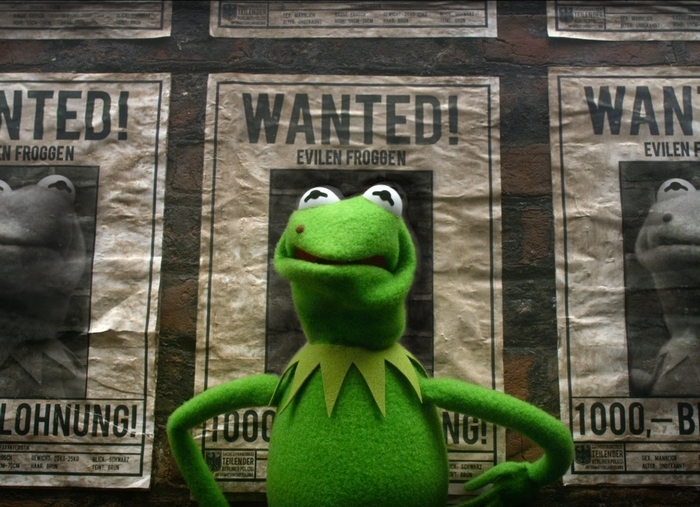 "Constantine, a Kermit the frog look-alike, in a scene from ""Muppets Most Wanted."""