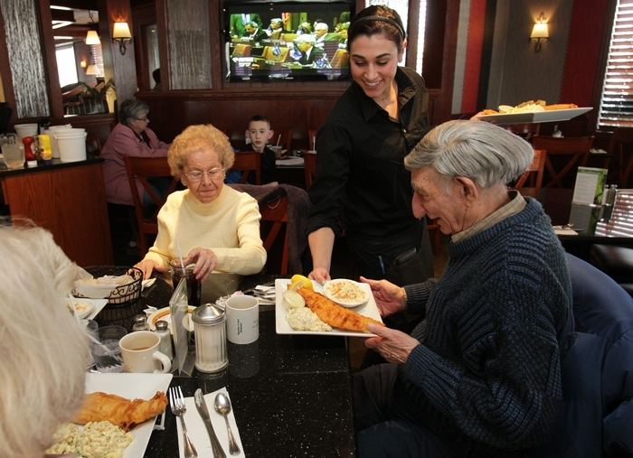The Gardenview on Union Road in West Seneca is open 24 hours.  Waitress Kelsey Maving serves fish fry dinners to Pat, left, and Sam Mendola of Buffalo. (Sharon Cantillon/Buffalo News)