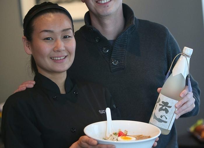 Chef Satomi Smith holds a bowl of Sato's popular ramen and owner Joshua Smith displays a choice of sake at Sato on Elmwood Avenue. (Robert Kirkham/Buffalo News)