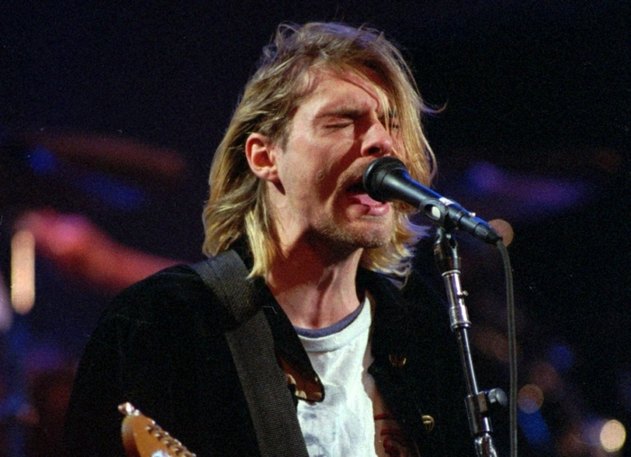 This Dec. 13, 1993 file photo shows Kurt Cobain of the Seattle band Nirvana performing in Seattle, Wash. It's been two decades since the Nirvana frontman took his own life yet he remains on in the thoughts of those he influenced and entertained. He's a touchstone for young musicians clutching guitars the world over and his story is a tale of both inspiration and caution. His influence still ripples across the surface of pop music and his shadow even looms in the hip-hop world where he's been a referenced by Jay Z, Kanye, Kendrick Lamar, Drake and Jay Electronica in various ways recently. (AP Photo/Robert Sorbo, file)