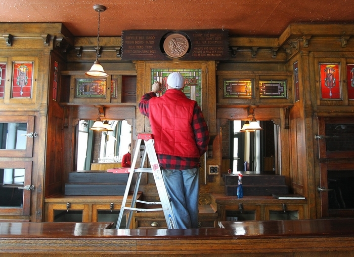 Sal Buscaglia works on cleaning an antique bar in Ulrich's in Buffalo on Feb. 14. (Mark Mulville/Buffalo News)