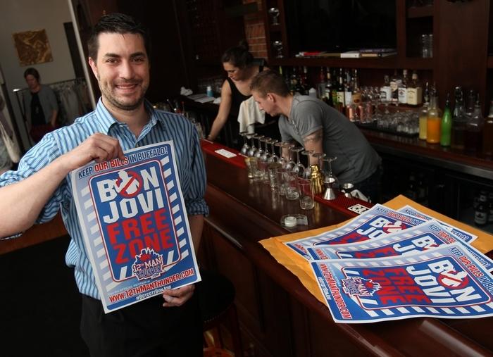 "Anthony Lynch hangs a ""Bon Jovi Free Zone"" poster at Savoy on Elmwood Avenue in Buffalo on May 21. move the Bills to Toronto. (Sharon Cantillon/Buffalo News)"