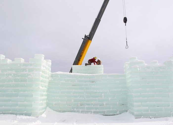 At top, Jim Bradford, left, and Tom Przepioka put blocks into place as they help build the ice castle in Mayville on Thursday. At left,  Bradford and Przepioka ice cut blocks. At center, Burl Swanson moves an ice block to the shore as he helps build the ice castle. At right, Przepioka and Bradford move the ice blocks into place. See a photo gallery at BuffaloNews.com. (Photos by Mark Mulville/Buffalo News)