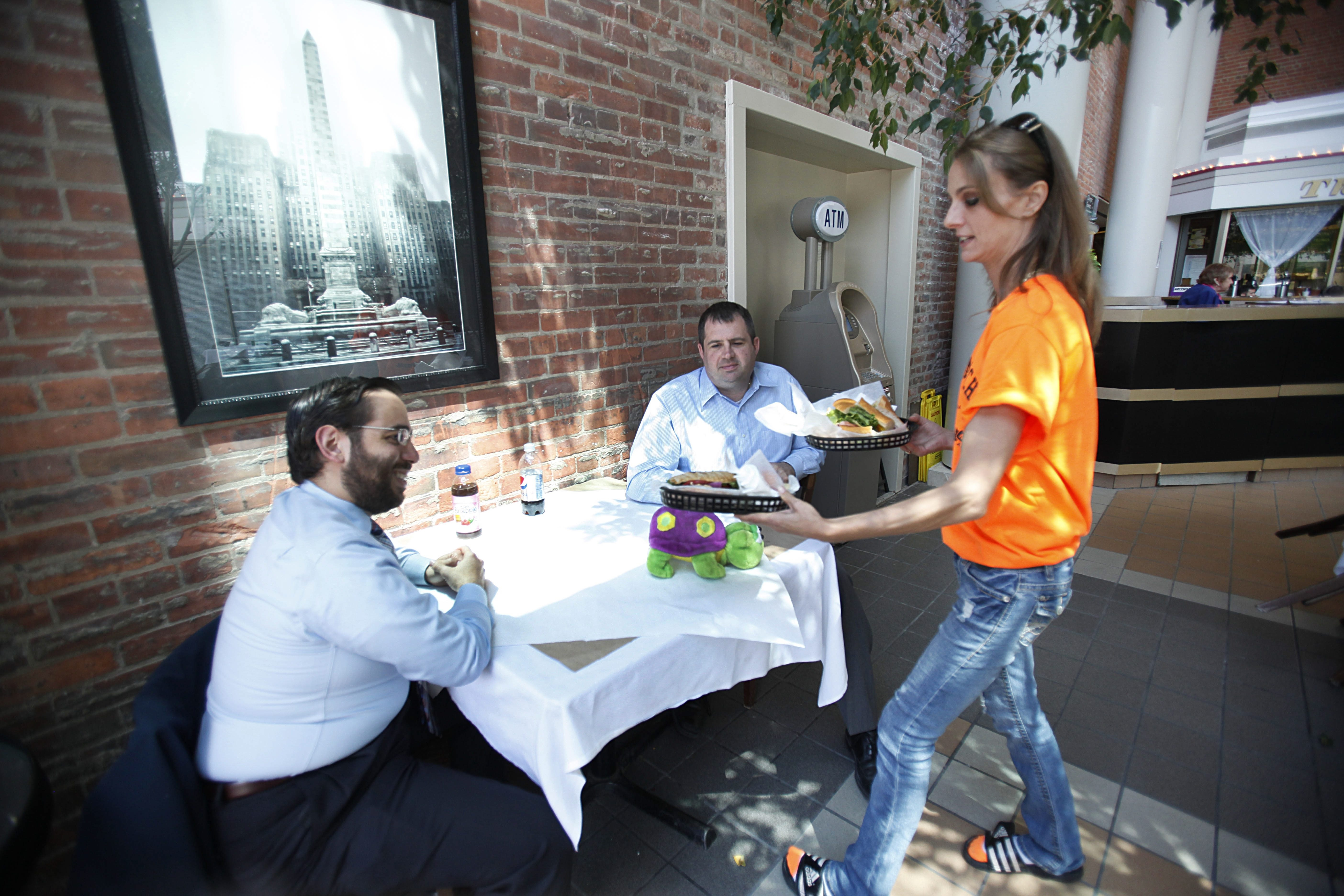 Tiffany Timineri serves Kevin Hinkley, left, and Mark Davis in the Gourmet Store.