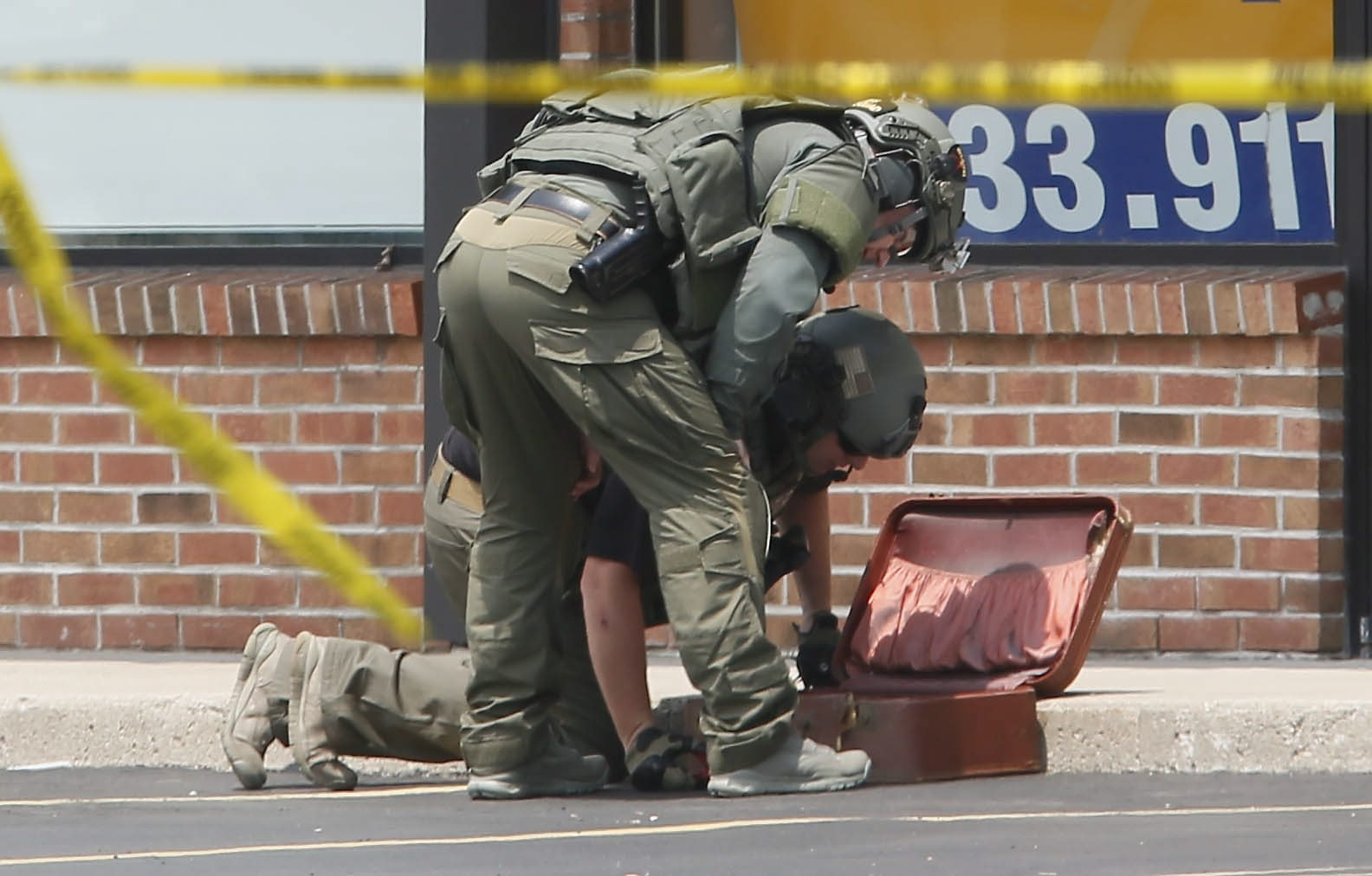 Erie County Sheriff's Bomb Squad officers inspect the suitcase that was removed from the Armed Forces Recruiting Center on Sheridan Drive after using a robot to remove it from the building Tuesday.