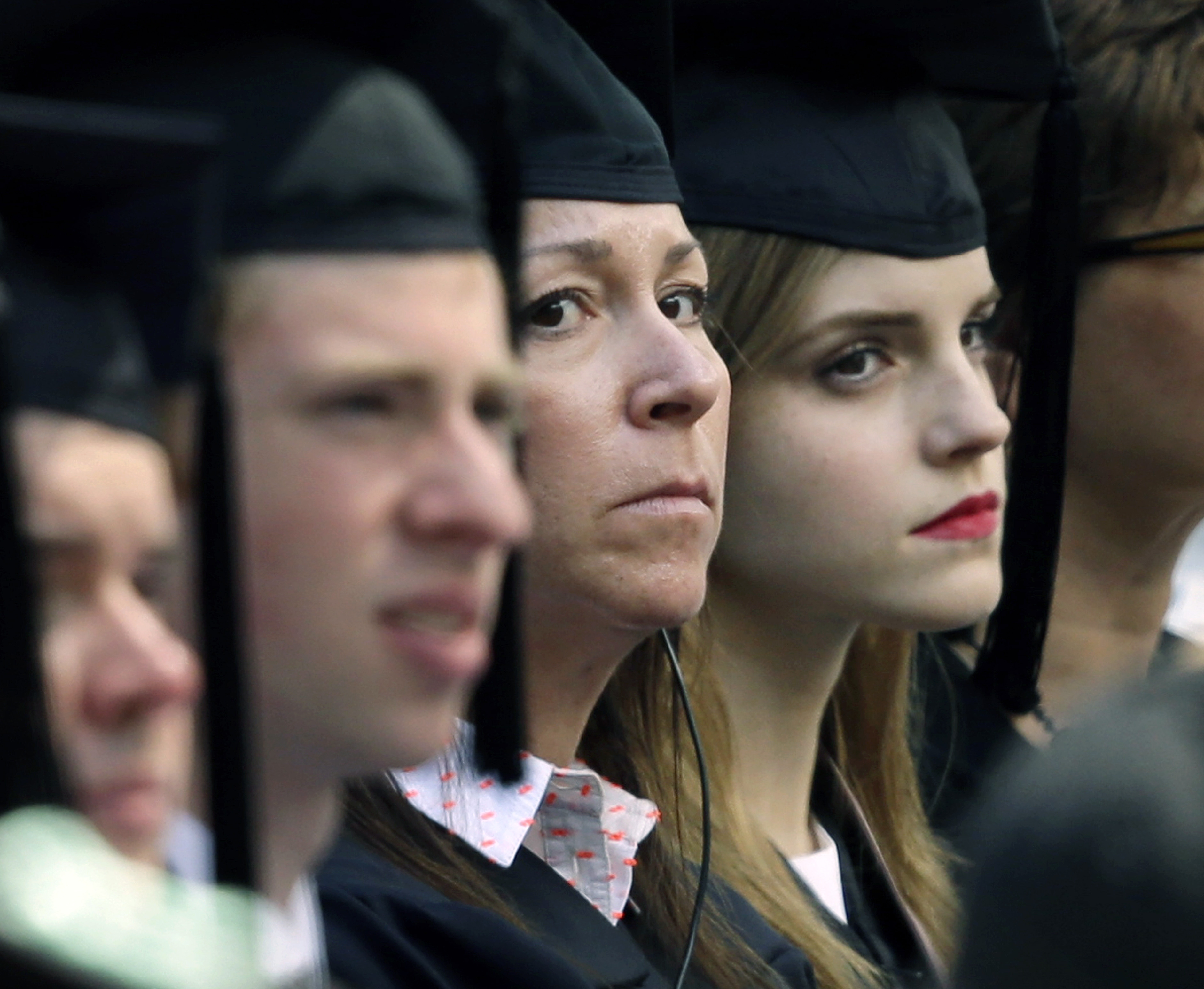 When actress Emma Watson, right, sat with fellow grads at Brown University's commencement Sunday, she was accompanied by an undercover armed guard, at left.